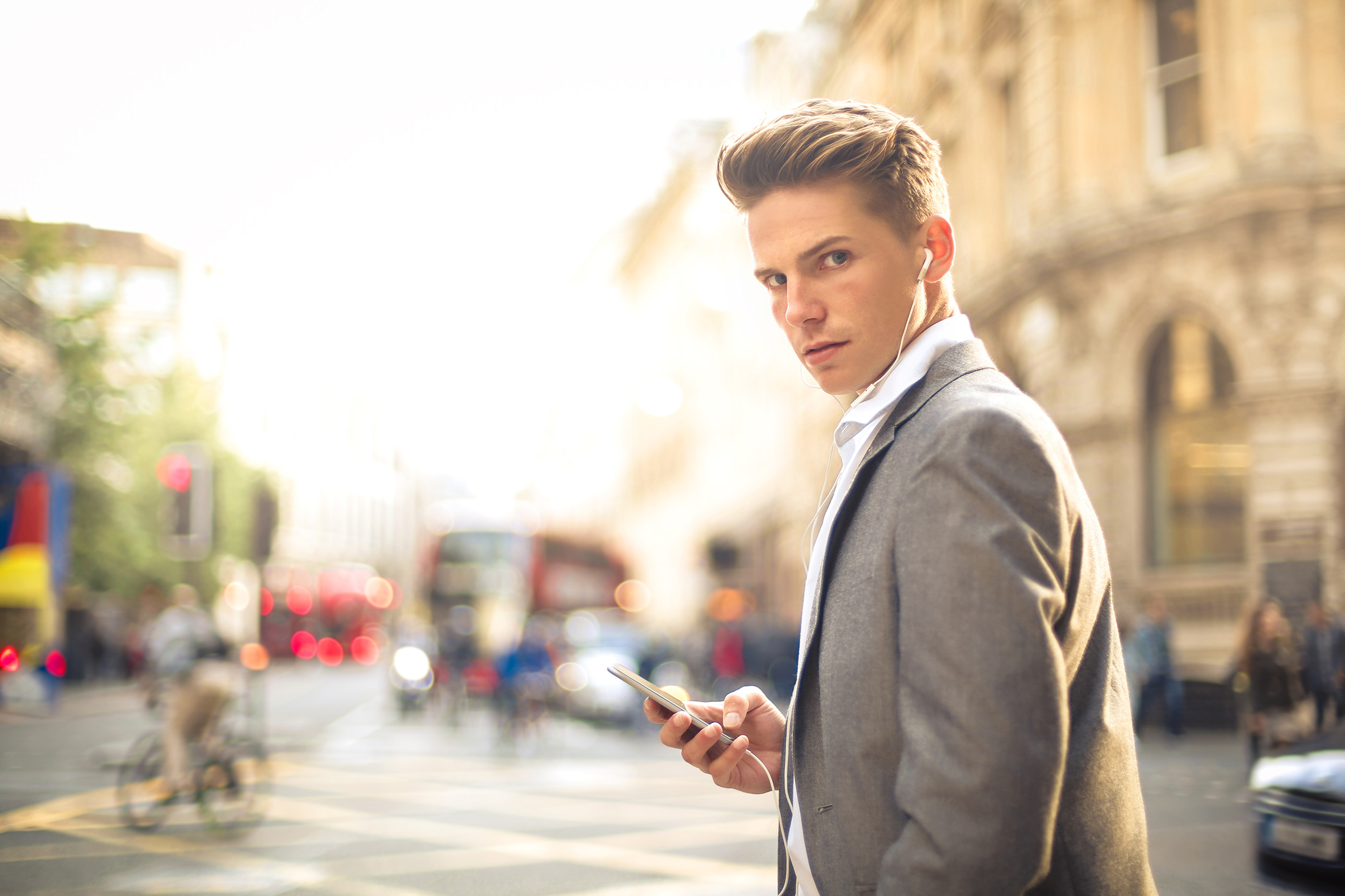 Young man in a busy street using a mobile phone