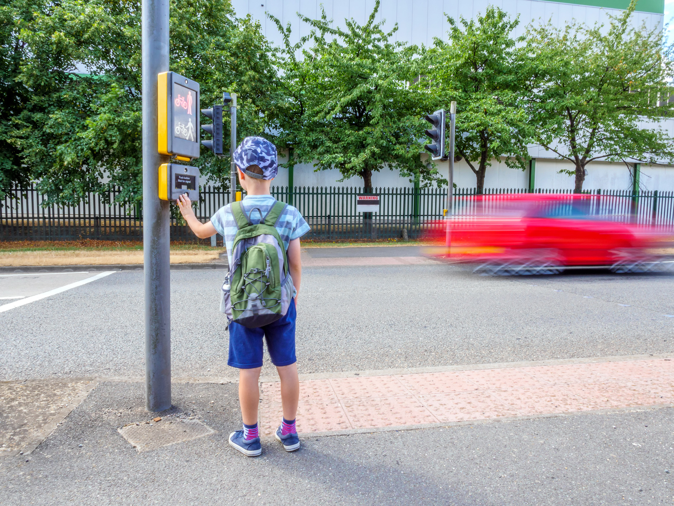 Young child waiting at a pedestrian crossing with timelapse of a moving red car in the background