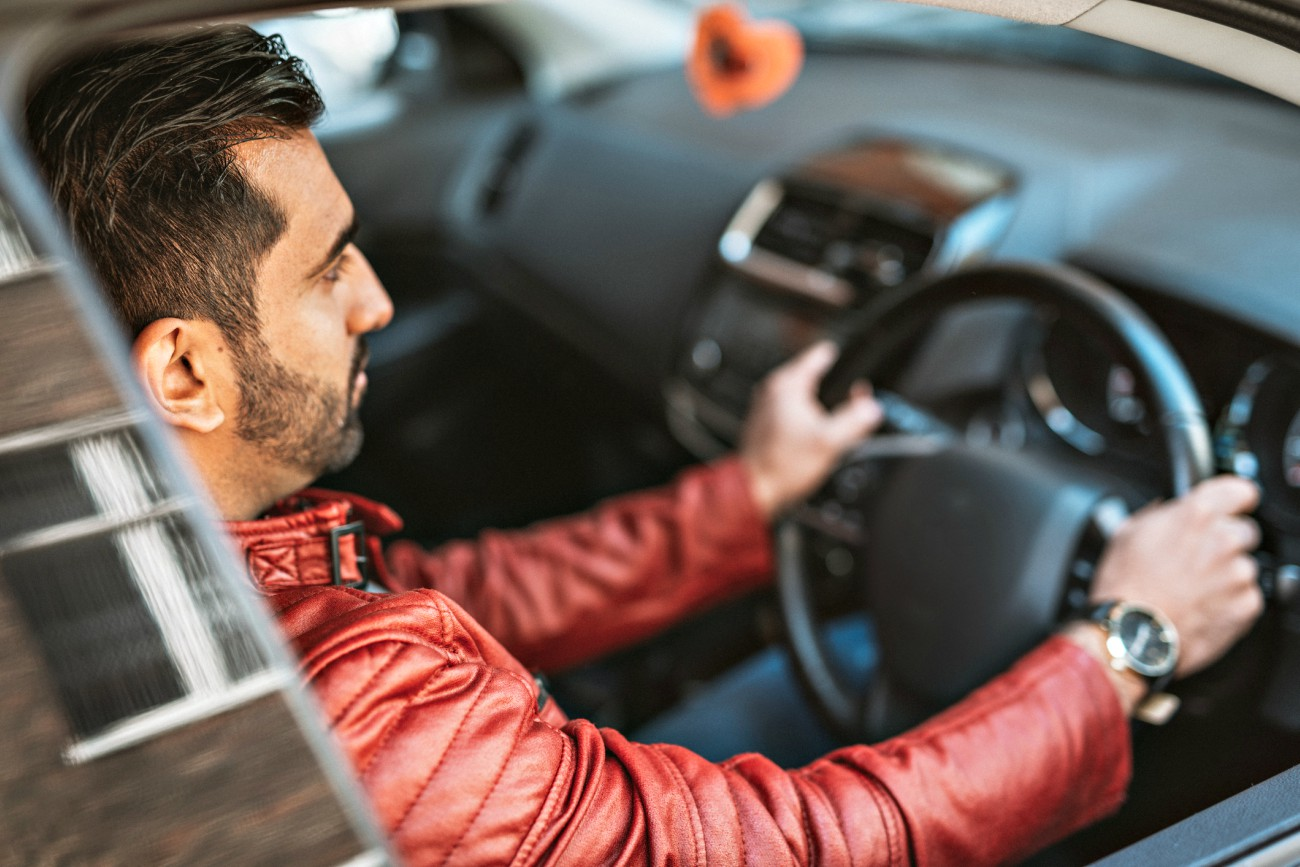 Young male driver sitting at the wheel and staring ahead