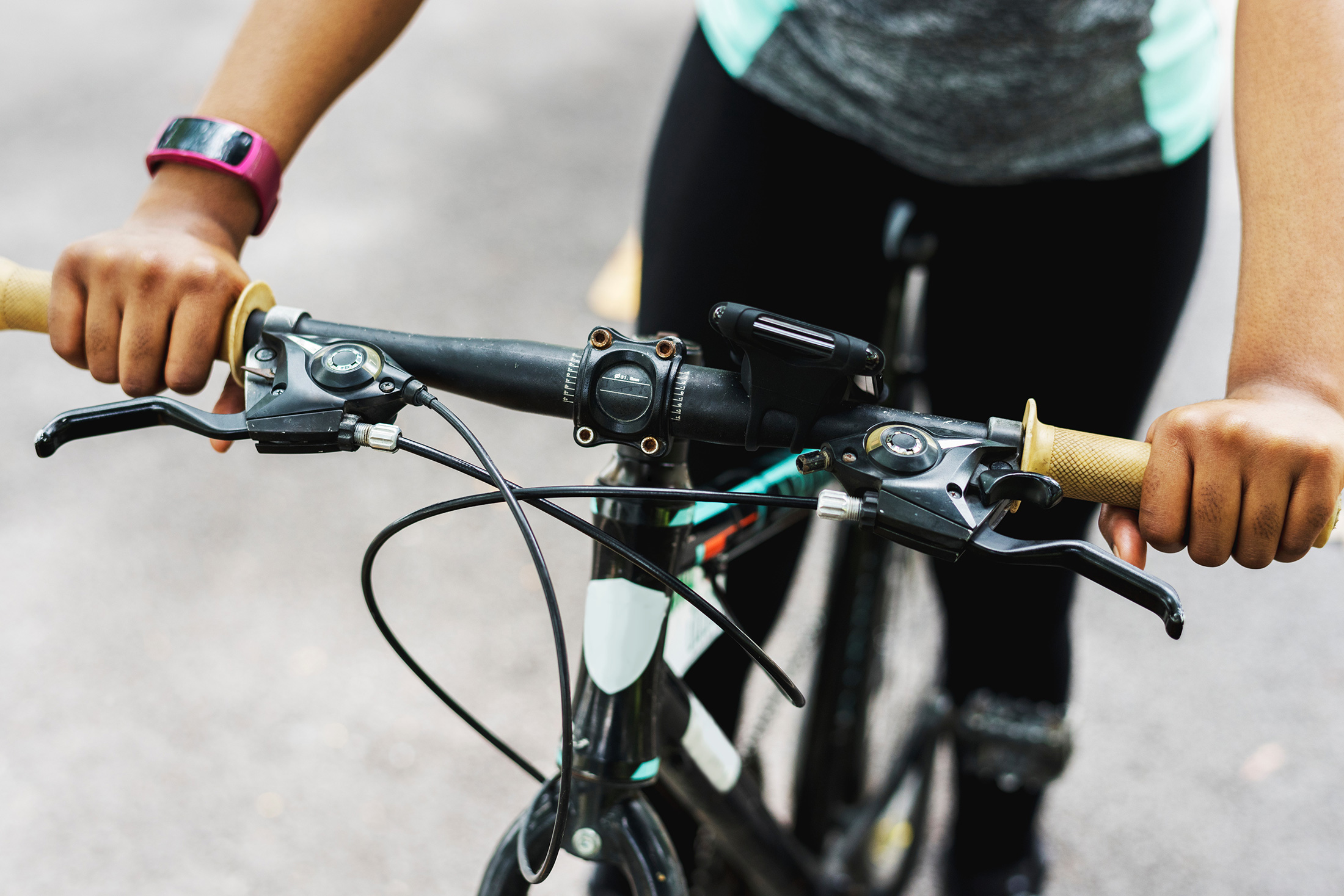 Close up of the handlebars of a bicycle partially showing the rider