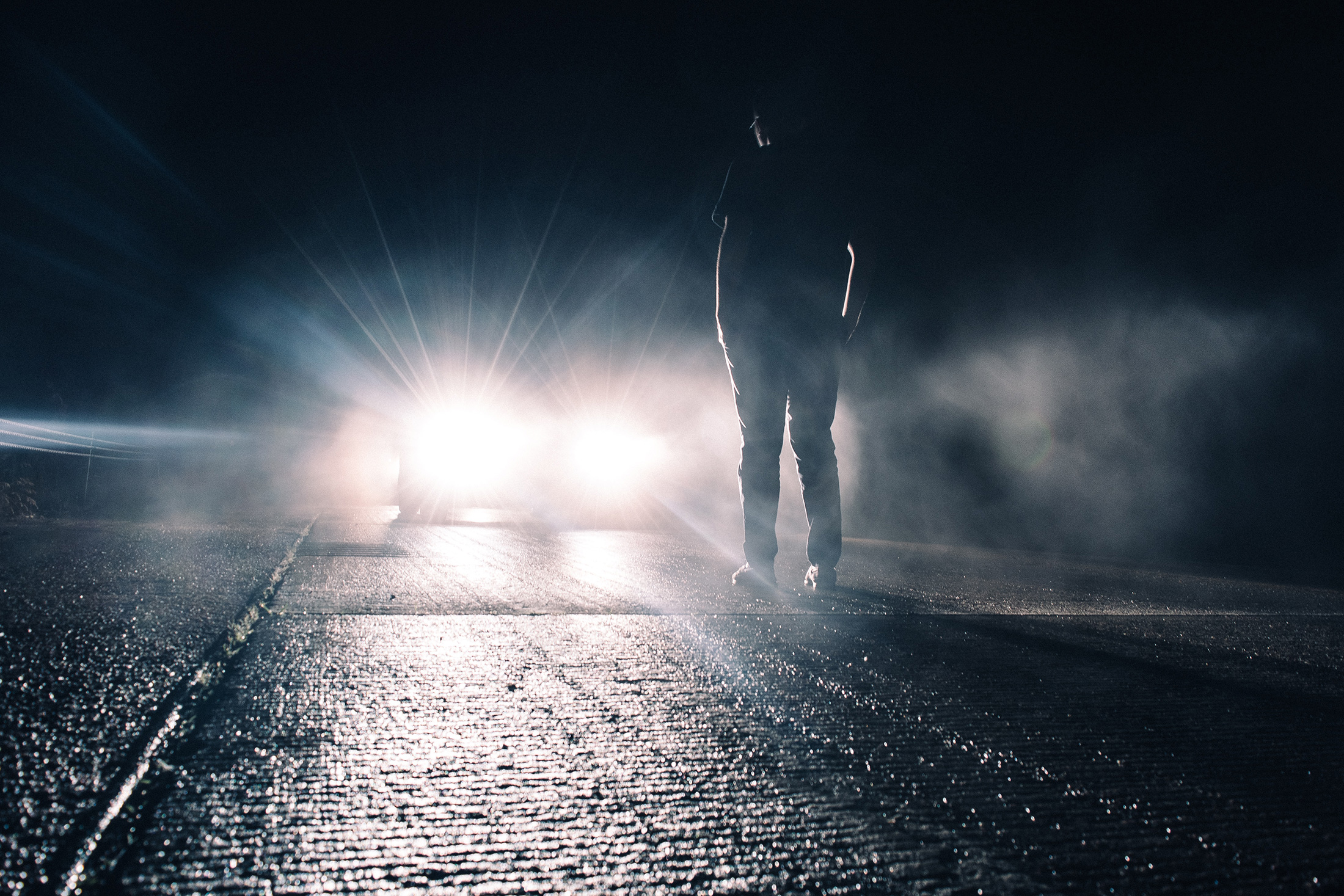 Young person standing in the middle of the road in front of an oncoming car
