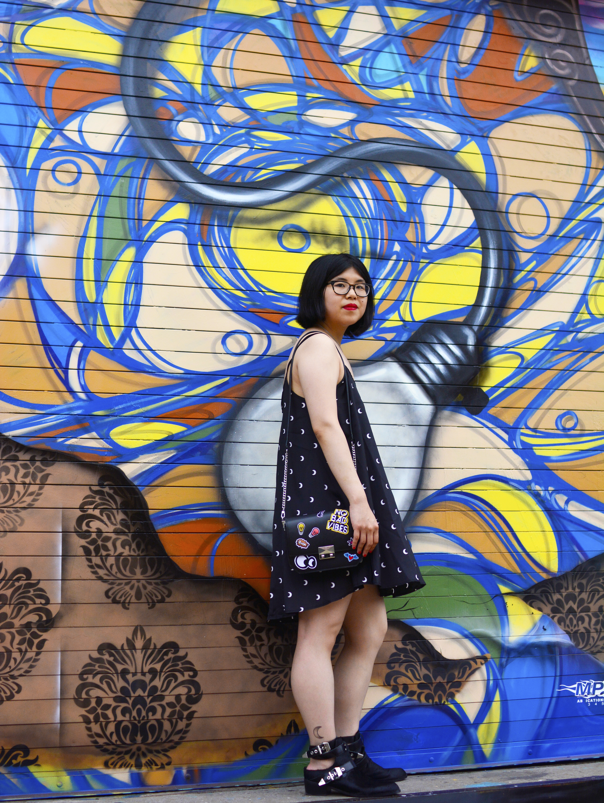 Discovering graffiti at the Welling Mural Court Project in Queens, NYC with a moon print dress, Sol Sana cut-out ankle boots, and ZARA crossbody bag with patches.