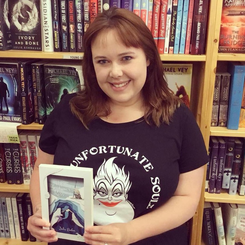 Me, wearing a very On-Brand Ursula T-Shirt and posing with my book in Powell's bookshop.