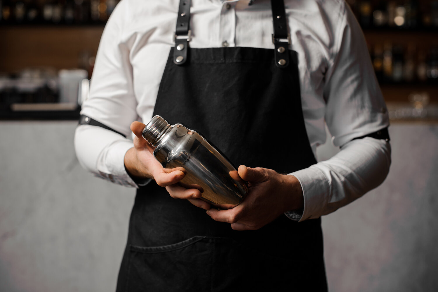 Barmans hands holding a shaker against the bar counter