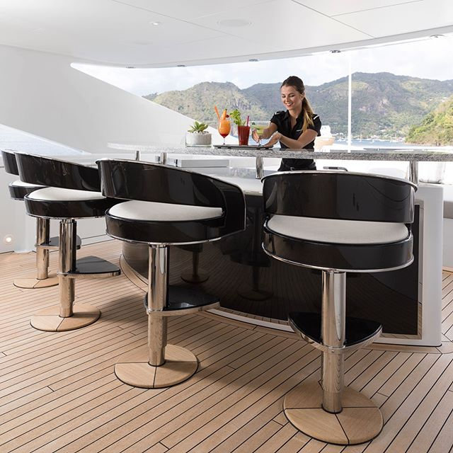Outdoor living enjoying cocktails while comfortably seating on a custom-designed rotating barstool made of marine grade stainless steel and polished carbon fiber panels designed by RADYCA and hand made by @glynpetermachin .⠀ .⠀ .⠀ #ramonalonsodesign #radyca #radycadesign #arquitecture #design #interiordesign  #decoration #decor #designconcept  #lifestyle #superyachts #yacht #luxury #superyacht  #architecture #onlyforluxury #UHNWI #megayacht  #luxurylifestyle ⠀ Builder: @heesenyachts⠀ Design: Radyca Design⠀ Photo: @jeffbrown.breedmedia