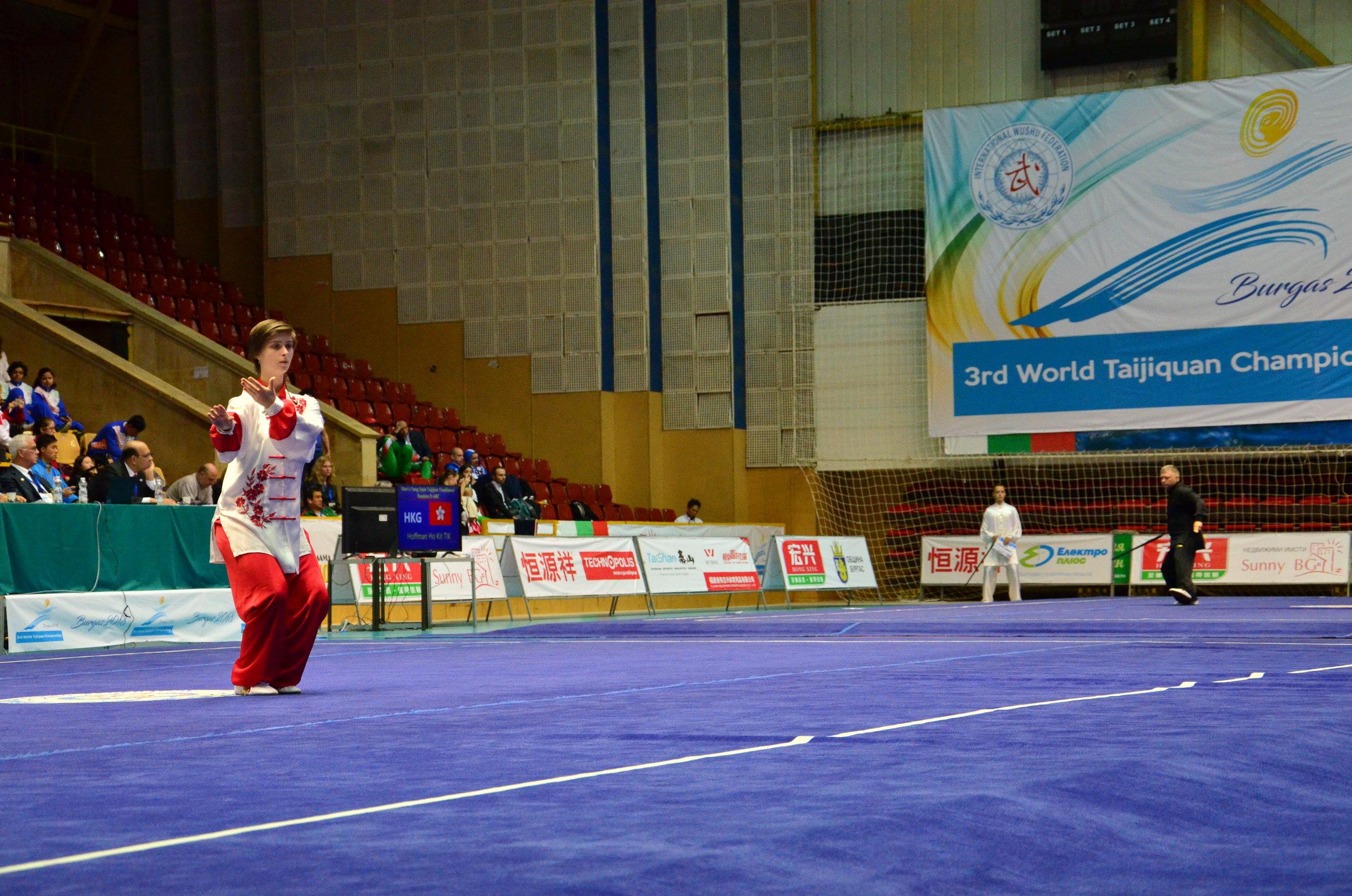 Na pierwszym planie Karolina Kulągowska startująca z formą ręczną Yang (Championship Events), w tle w czarnym stroju Tomasz Dybicz z tradycyjną formą Yang z mieczem (Demonstration Events).