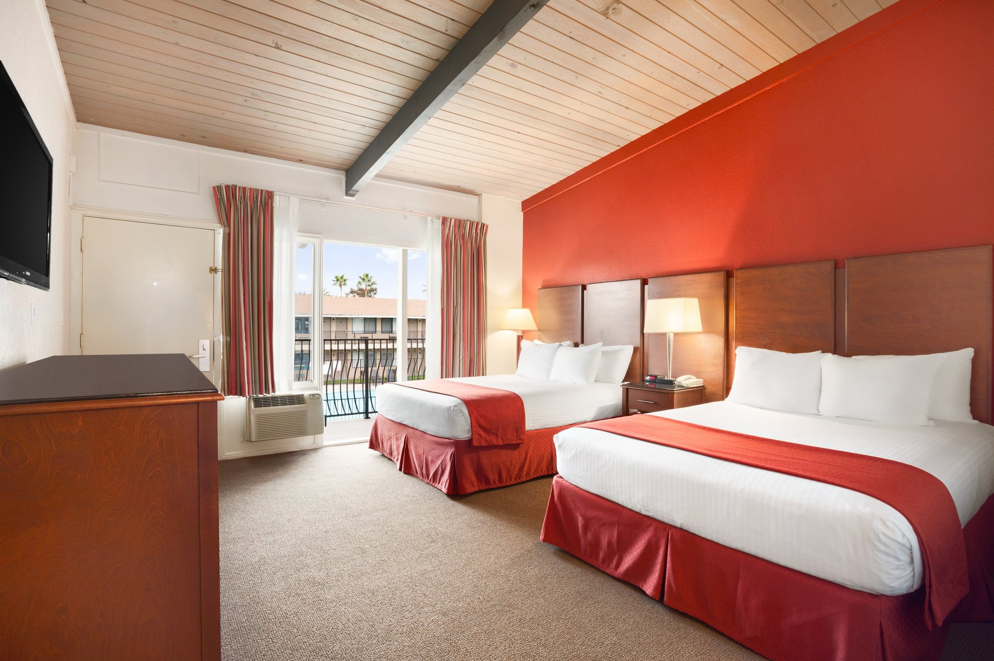 Courtyard Two Queen - Enjoy views of our tranquil courtyard from this charming guest room! Perfect for a relaxing group getaway, this room boasts two soft queen beds, a mini-fridge, a microwave, and a flat-screen TV. Our Courtyard Two Queen offers sprawling views of our courtyard and pool. Our property is punctuated by well-manicured grounds and greenery like palm trees.Max 4 Guests 2 Queen Beds