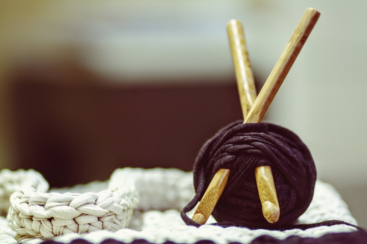 Closeup of a small brown ball of yarn with two wooden crochet hooks inserted.