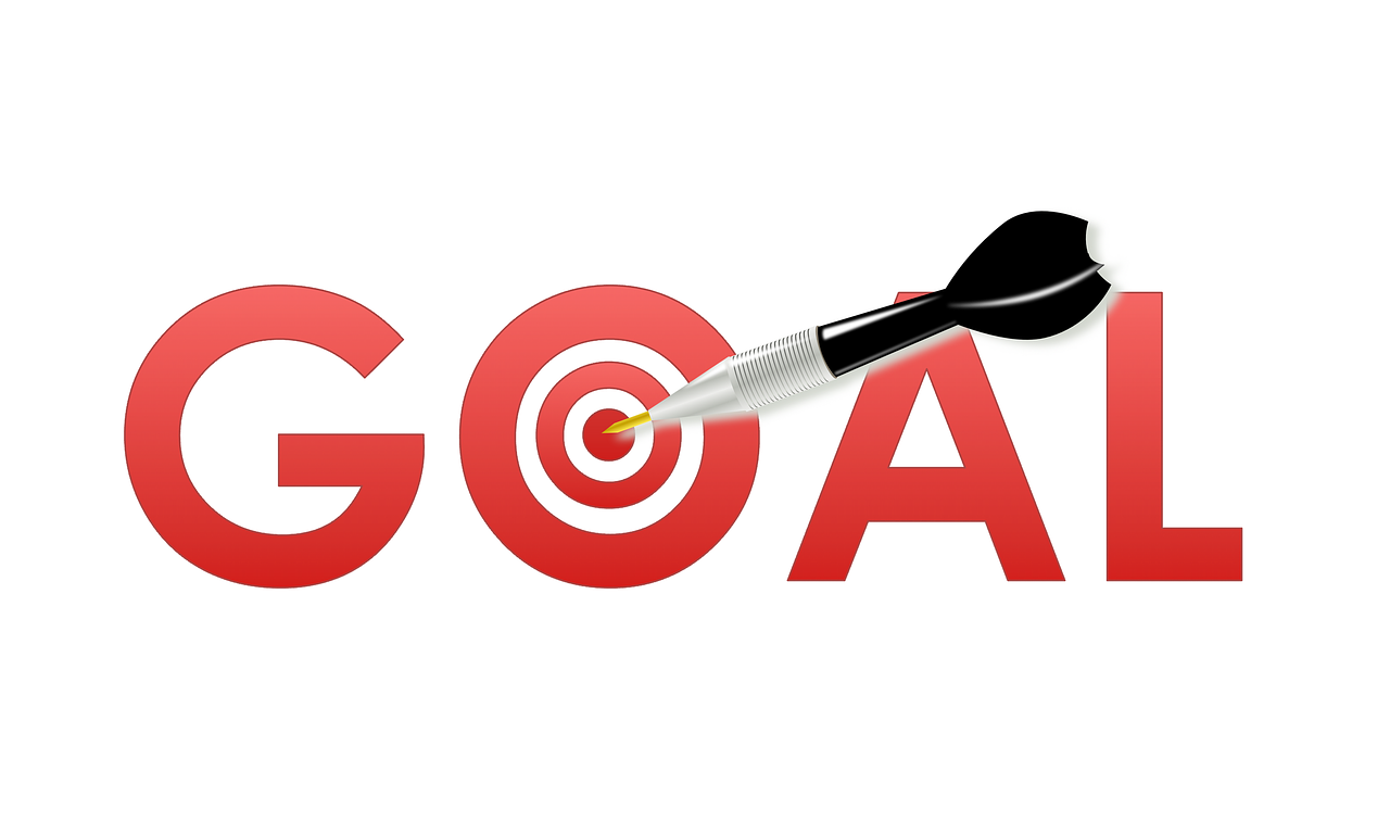 GOAL written in red ink with black and silver dart centered on a dartboard in place of the O.