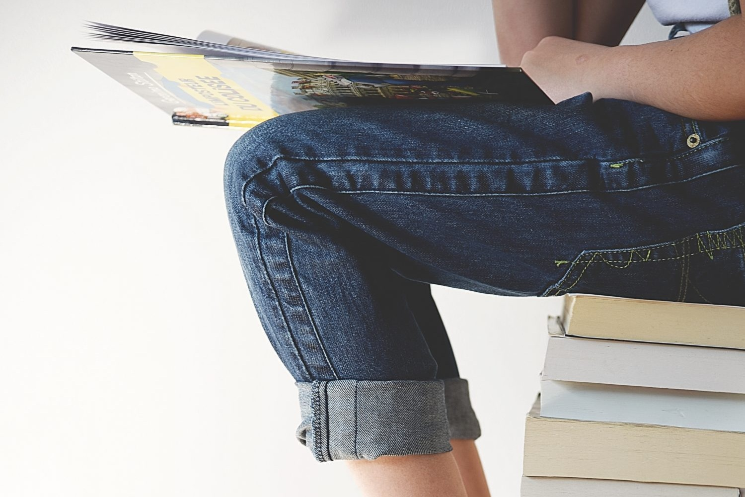 Person seated on stack of books, close-up of bare feet and jeans
