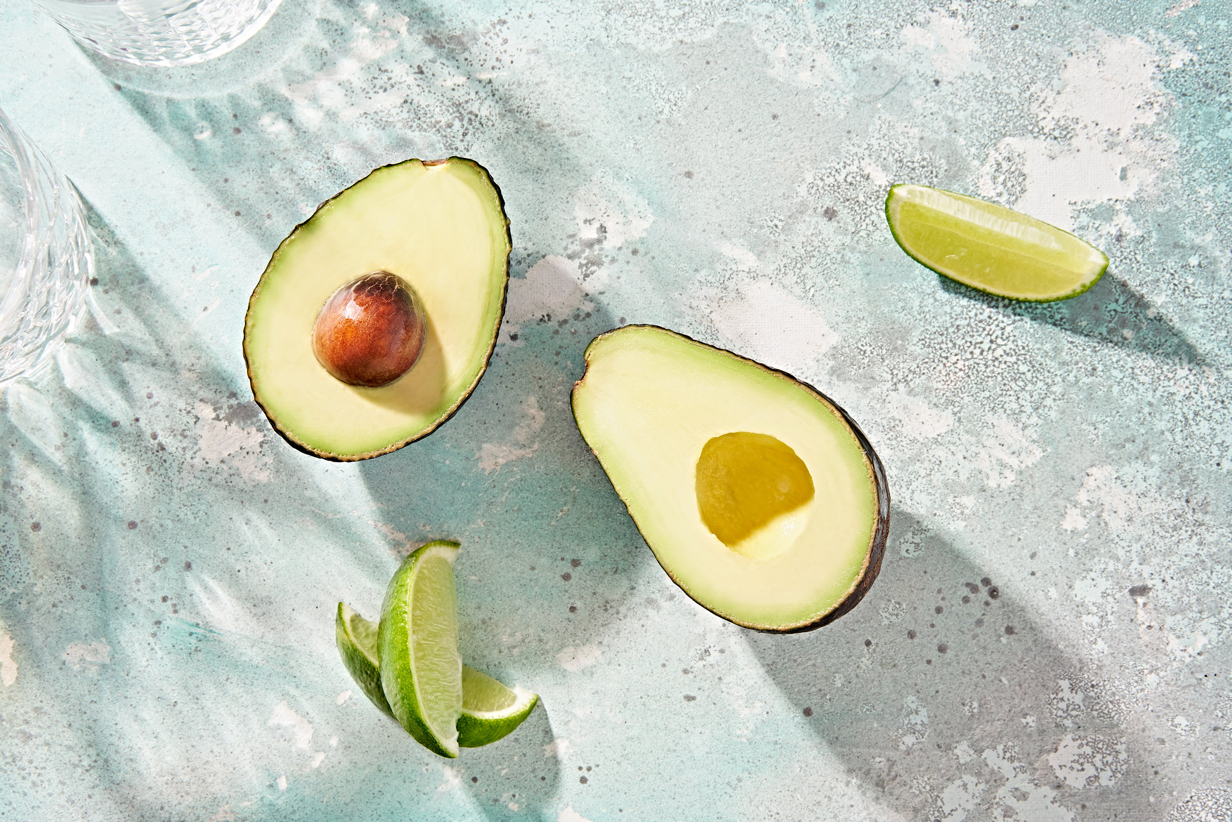 Perfect avocado halves with lime wedges