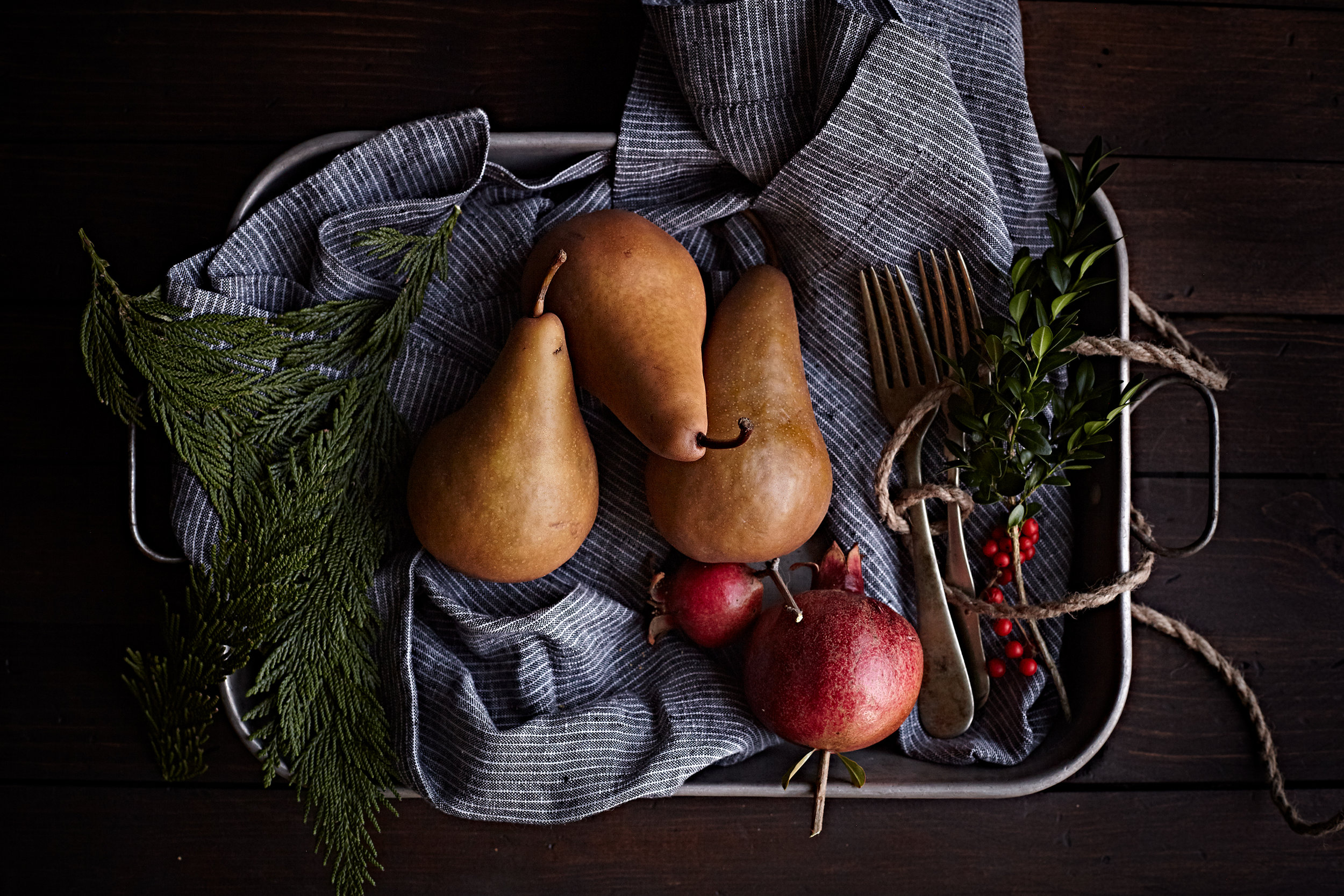 Bosc pears and pomegranate on a tray with napkin and foliage