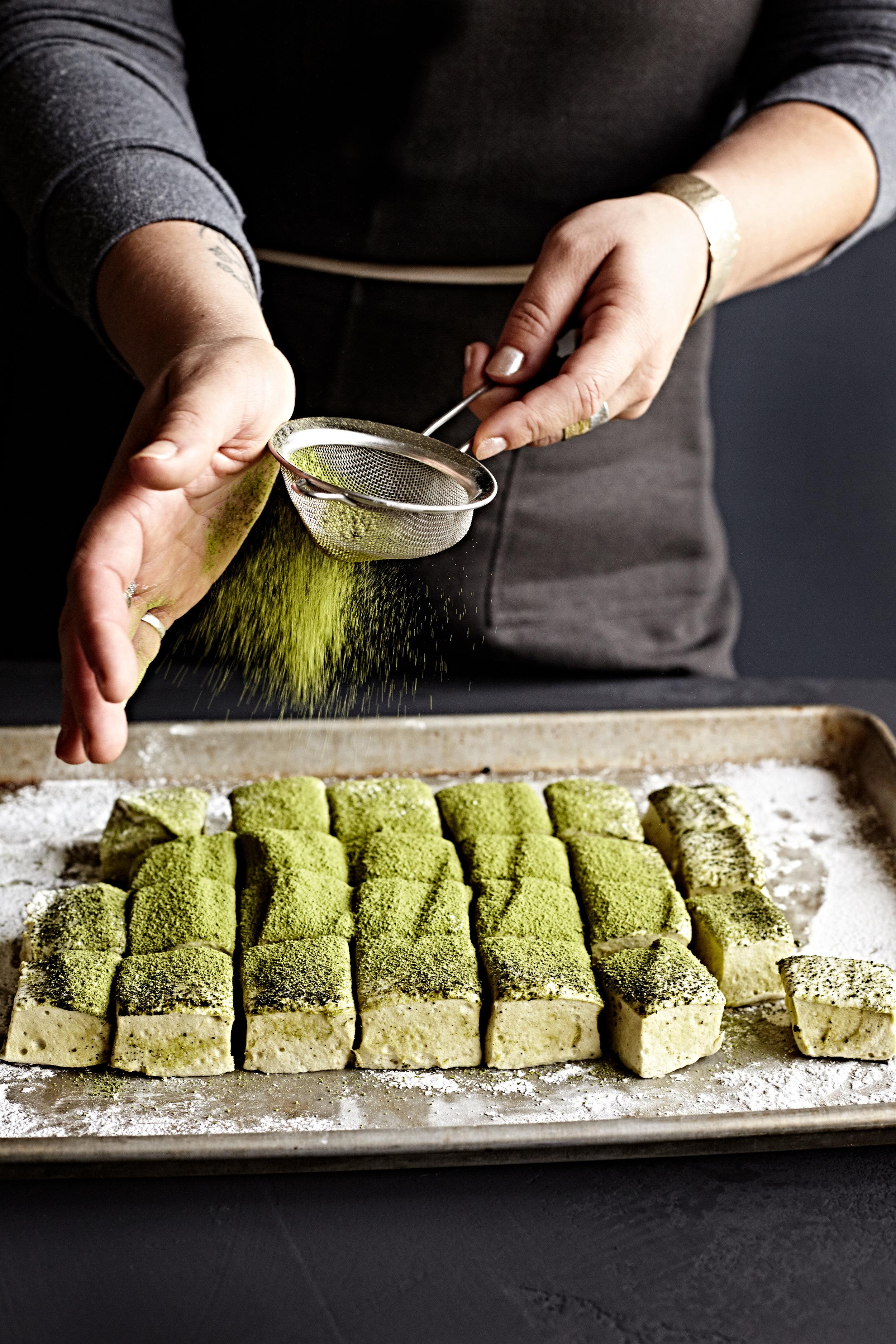 Woman's hand shaking matcha green tea onto homemade matcha marshmallows