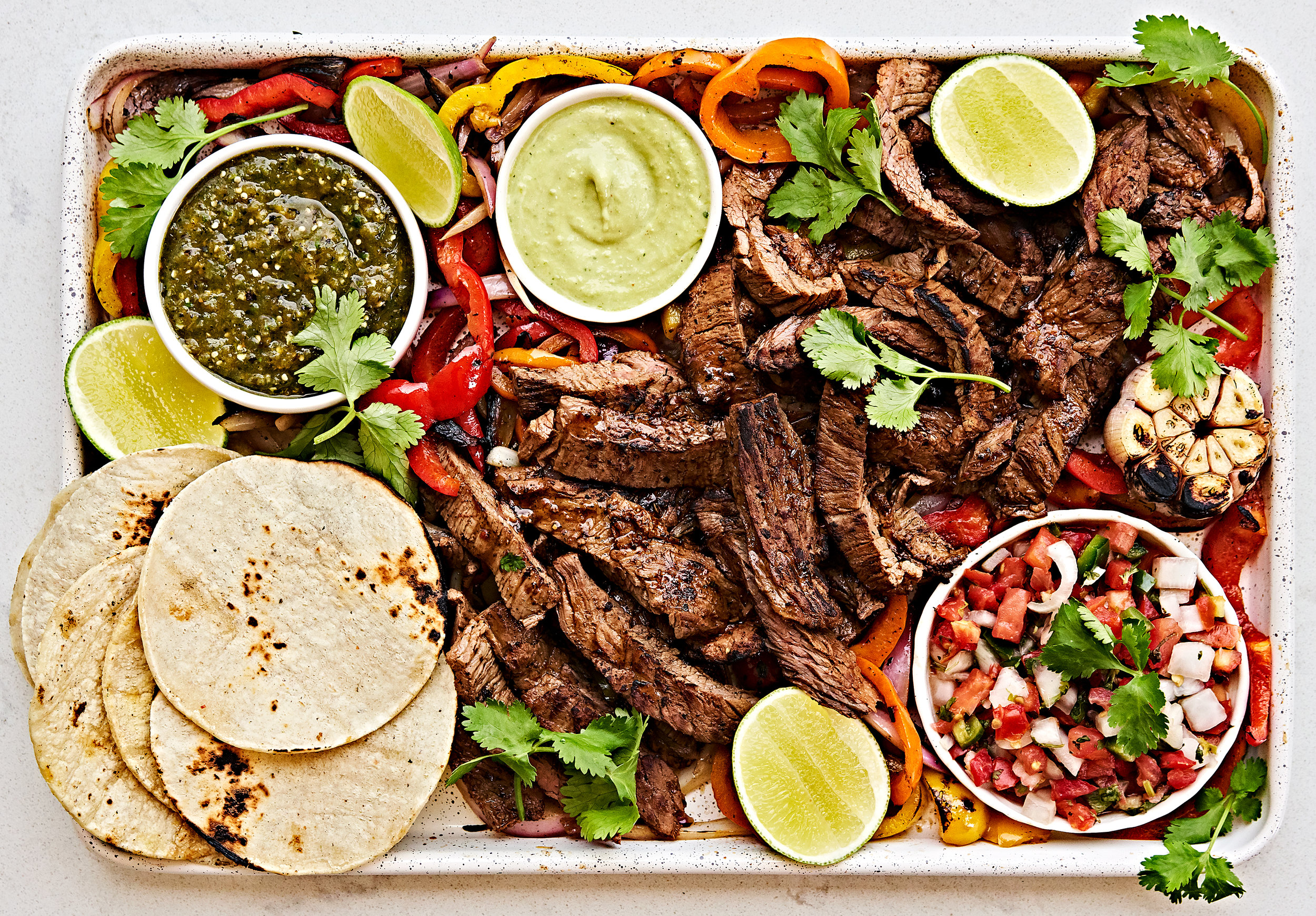 Flank steak fajitas platter with homemade salsa verde, sauteed peppers and onions, avocado crema and tortillas