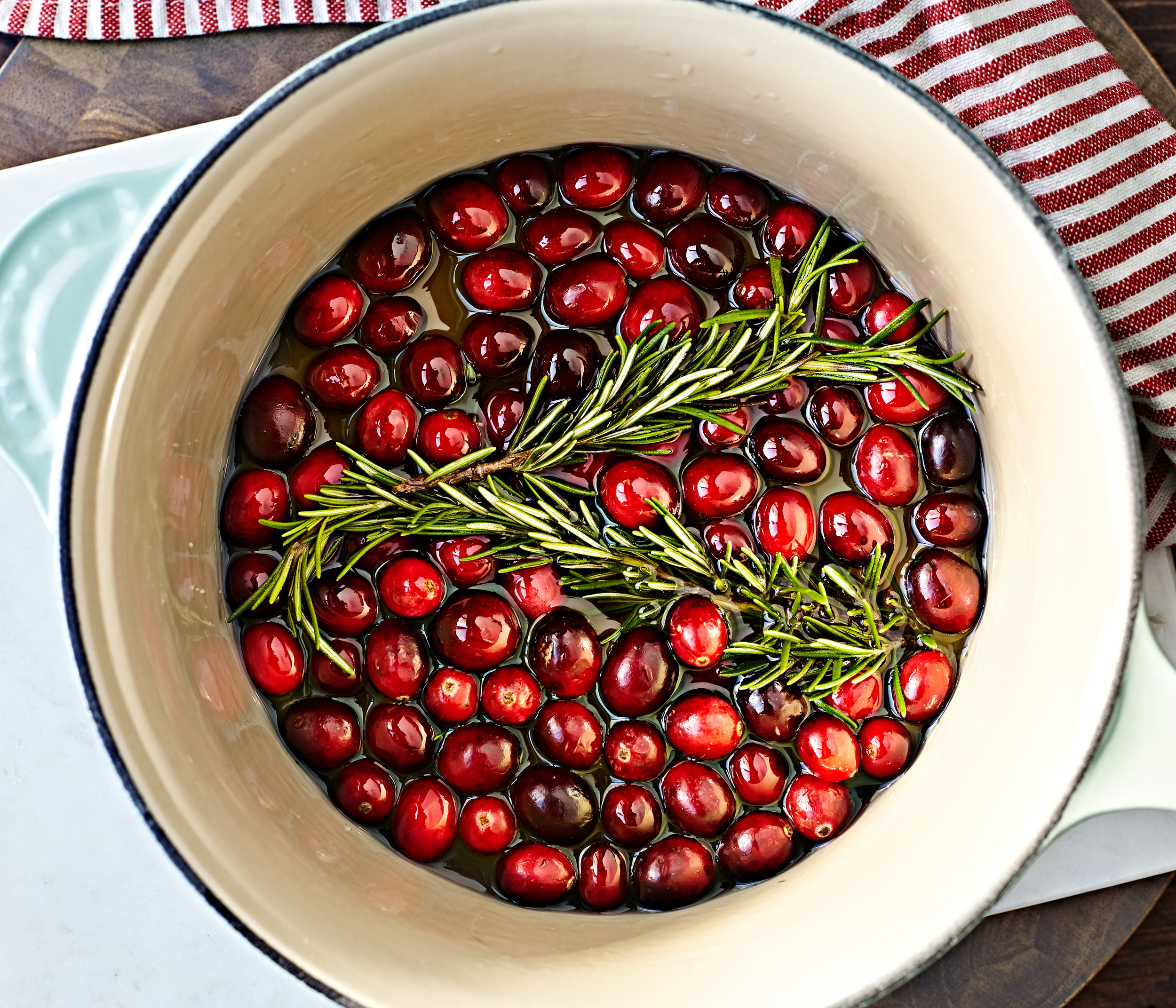Fresh cranberries steeping in simple syrup with rosemary sprig
