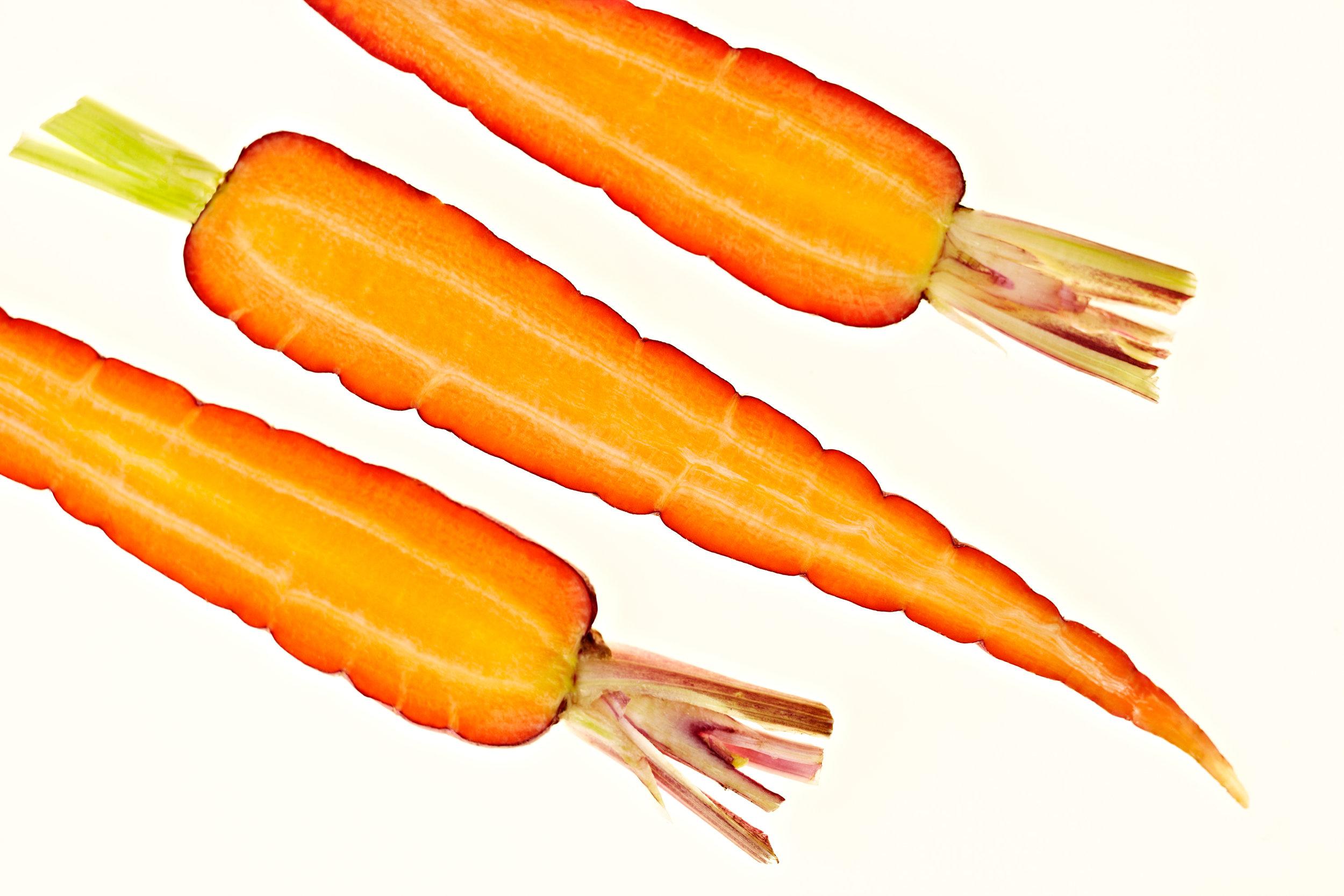 Overhead shot of sliced carrots on white