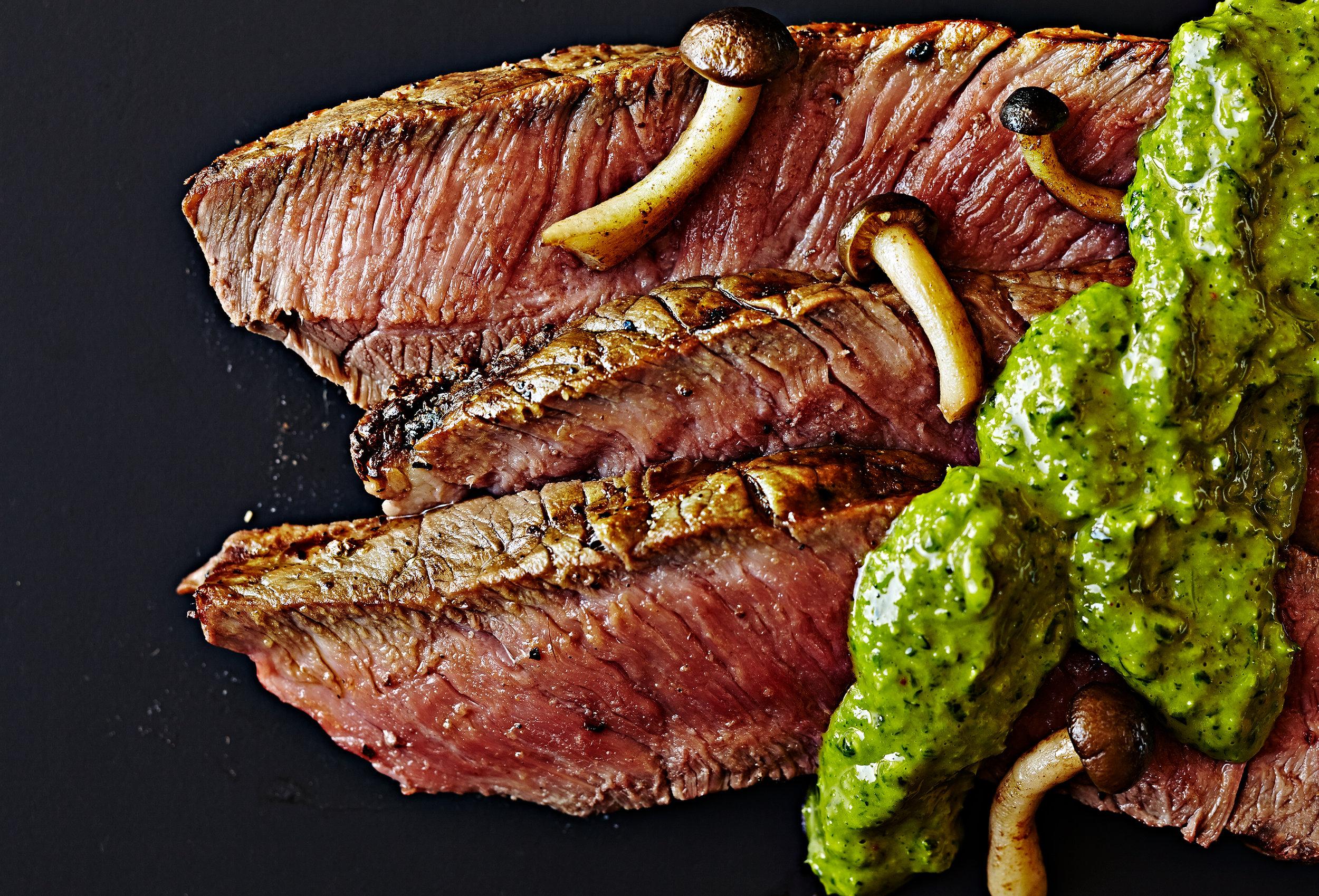 Medium rare steak slices with mushroom and chimichurri  on black background