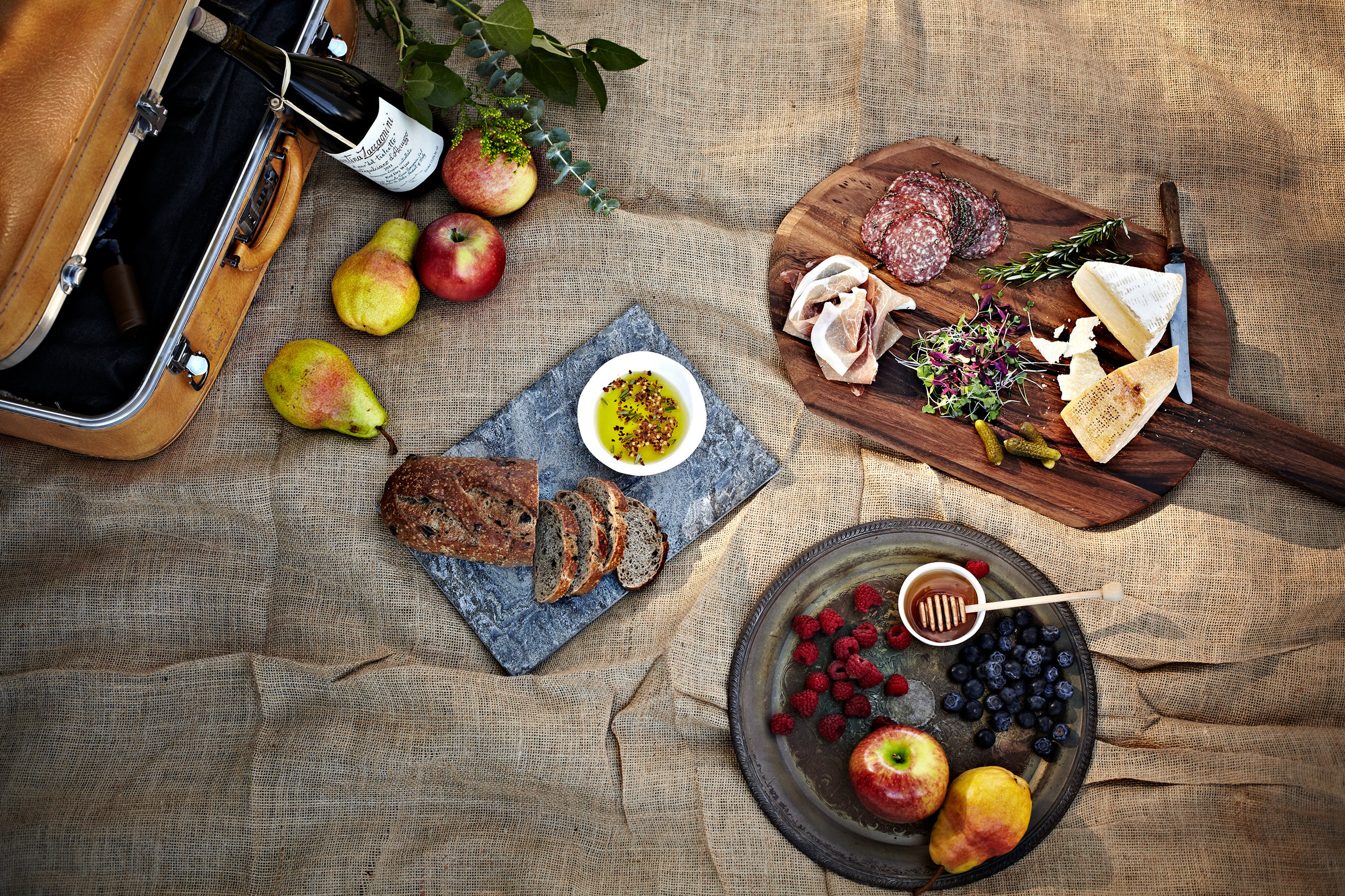 Spanish picnic with dappled light, charcuterie board, fruit, and wine