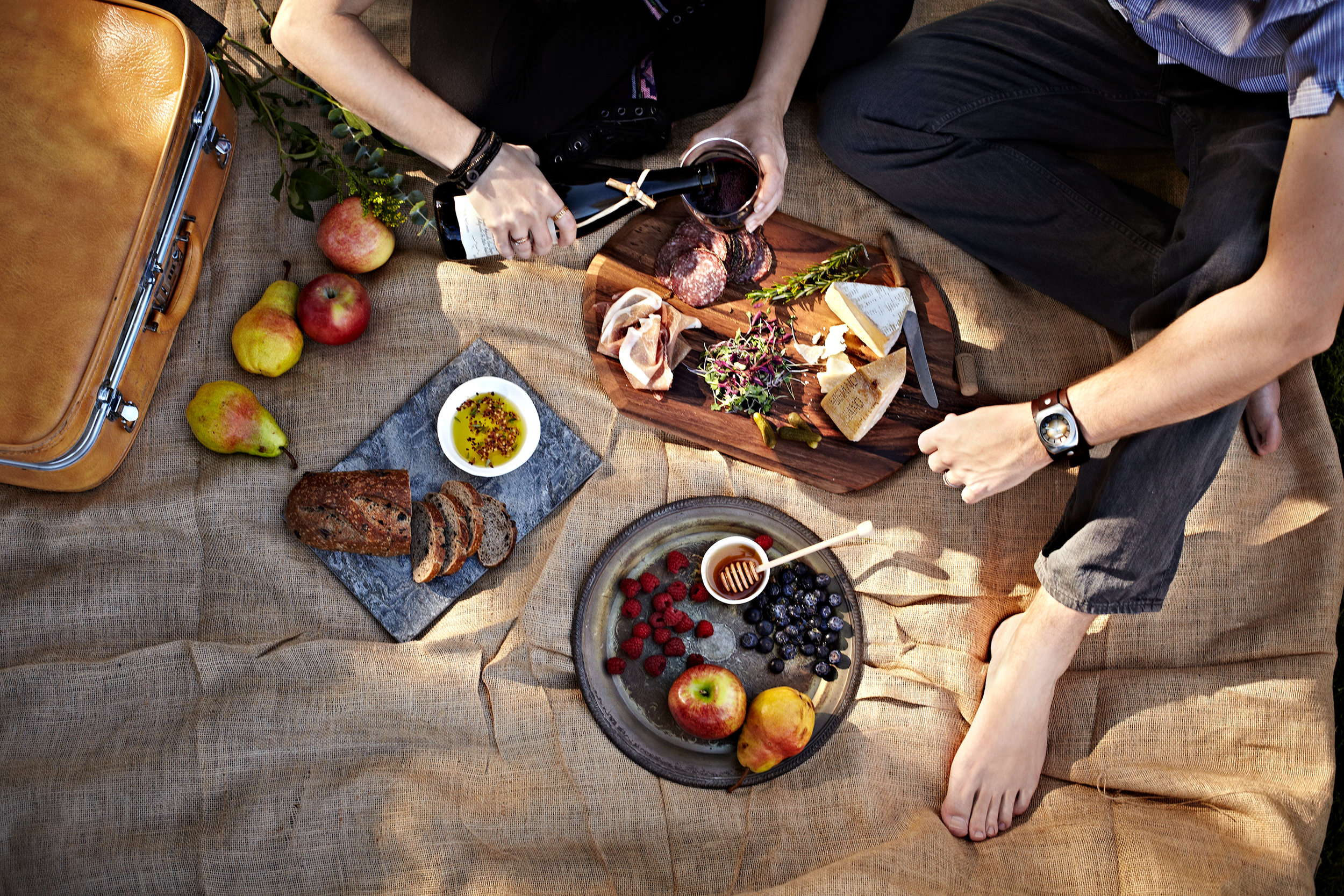 Couple having a Spanish picnic with dappled light, charcuterie board, fruit, and wine