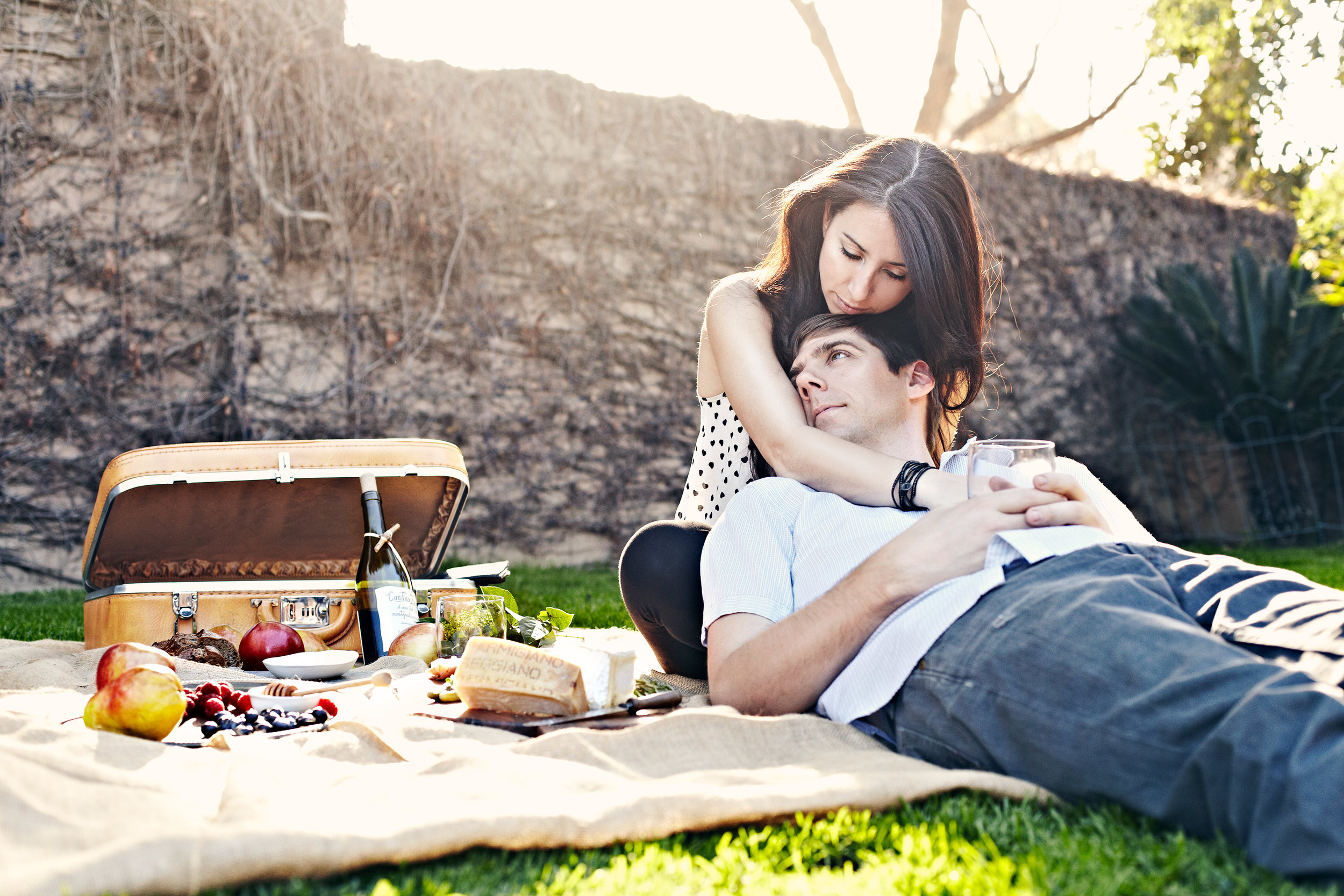 Couple embracing having a Spanish picnic with dappled light, charcuterie board, fruit, and wine
