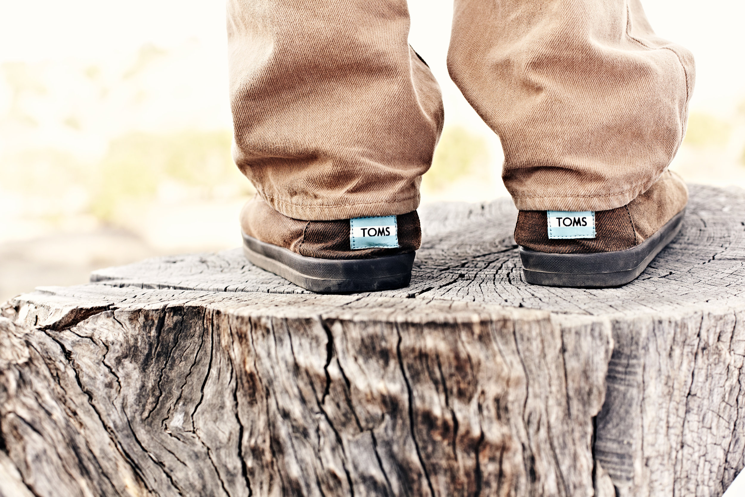 Man standing on tree stump in Tom's shoes