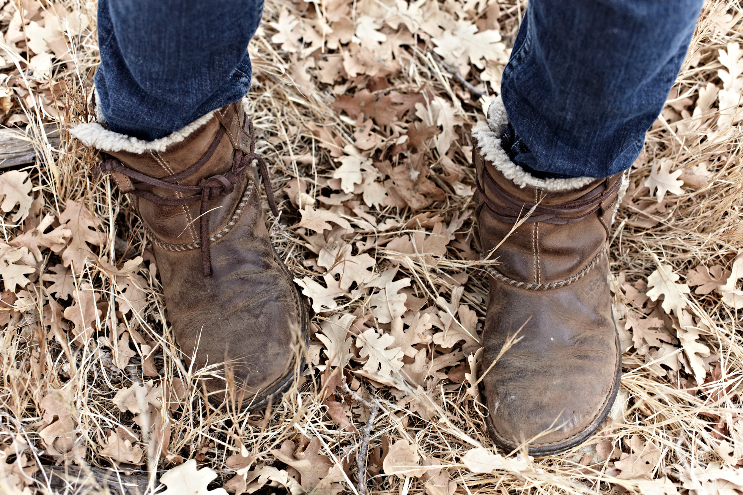 Young woman standing in fallen oak leaves wearing Ugg boots