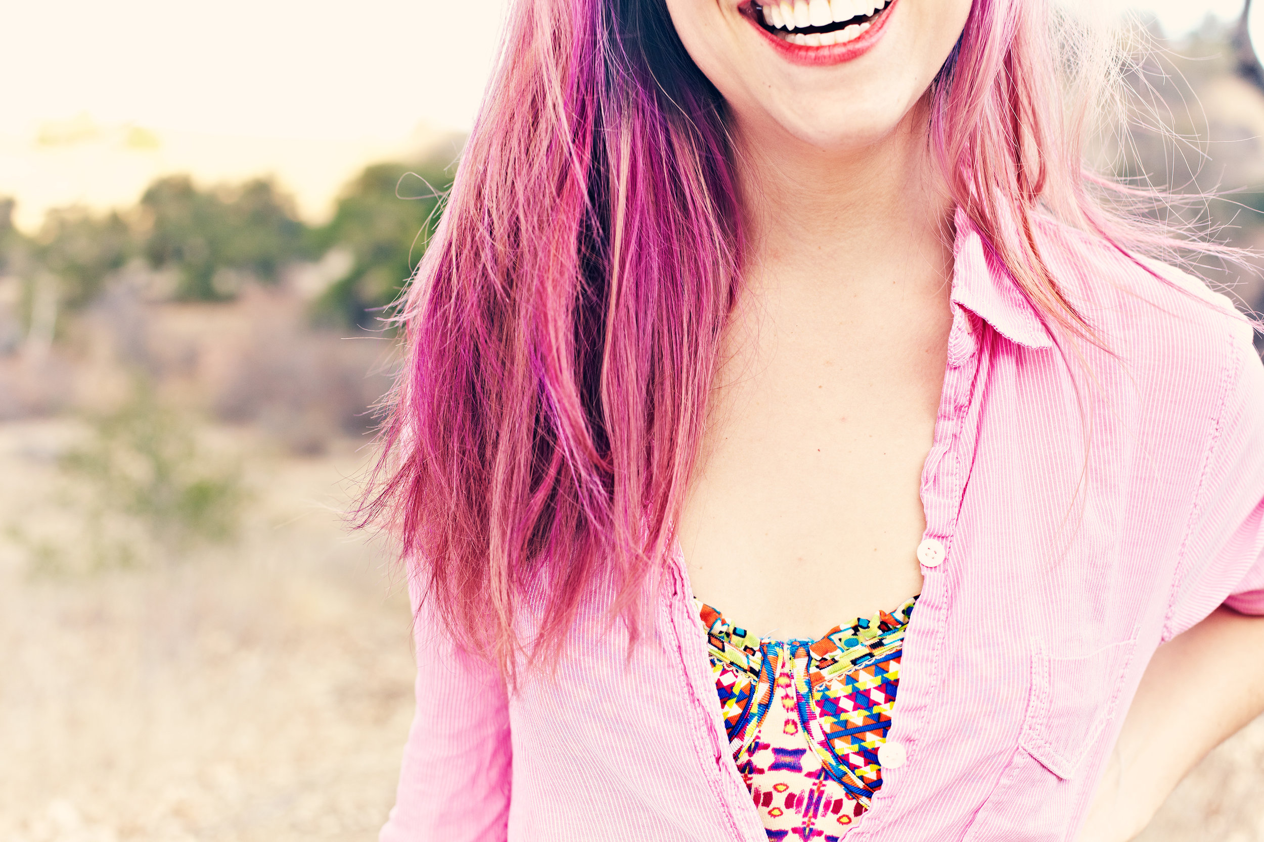 Pink haired young woman smiling on desert mountain scene