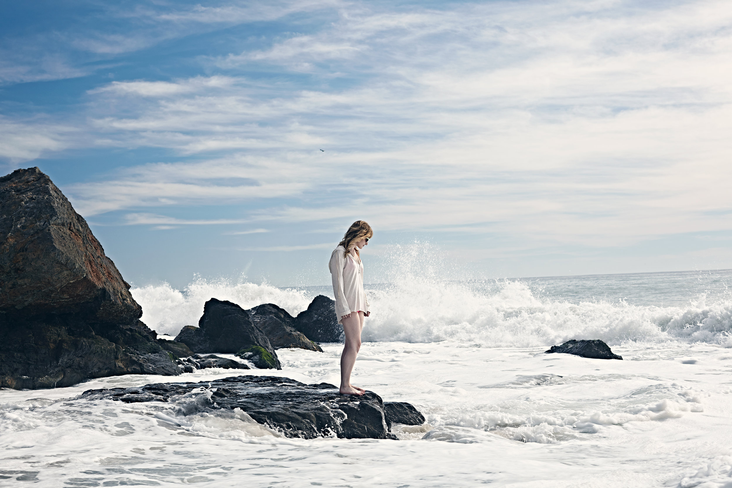 Young woman standing alone on a rock in the ocean