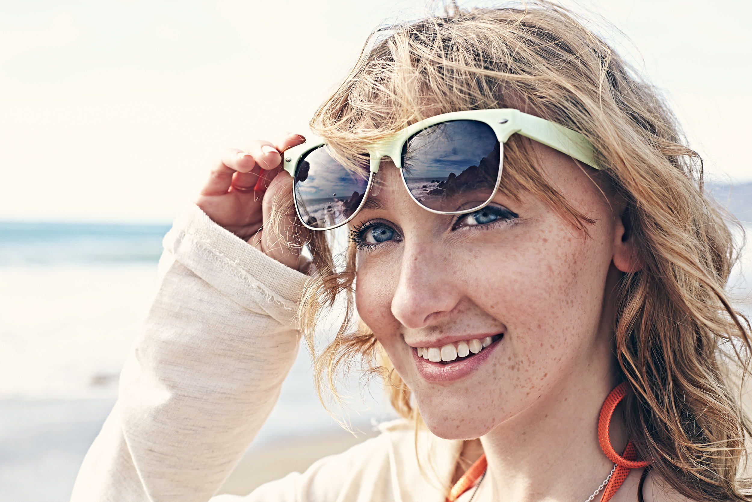 Young woman in sunglasses on the beach