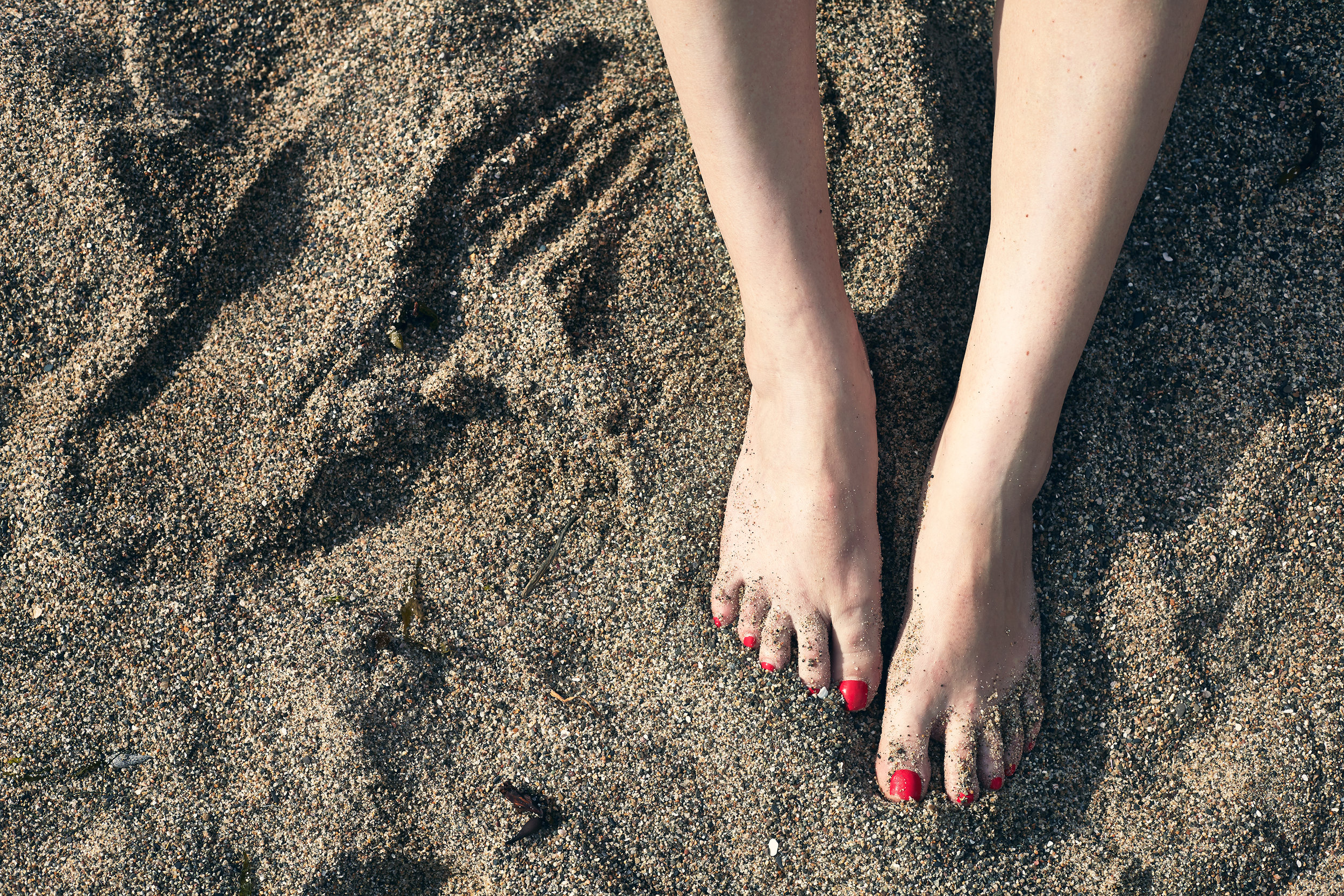 Pink painted toenails feet in the sand