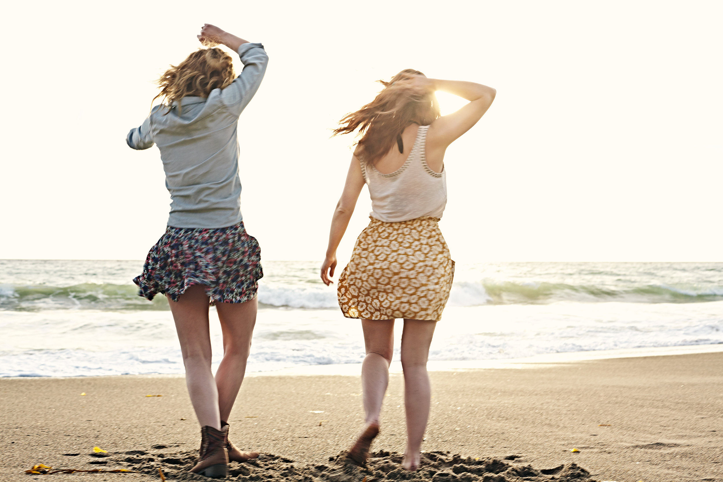 Two young women dancing in the sunset at the beach