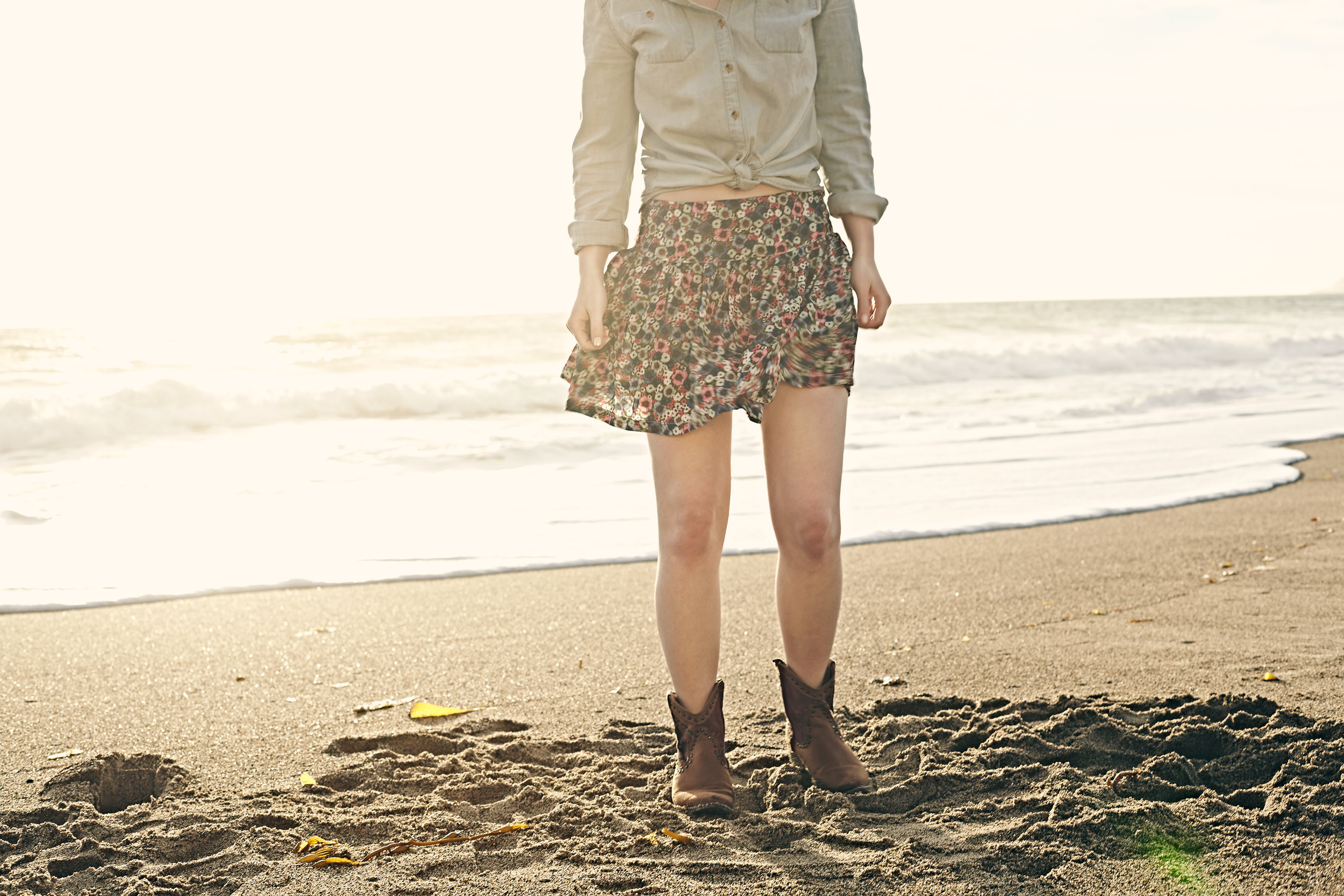 Young woman in skirt at the coastline beach at sunset