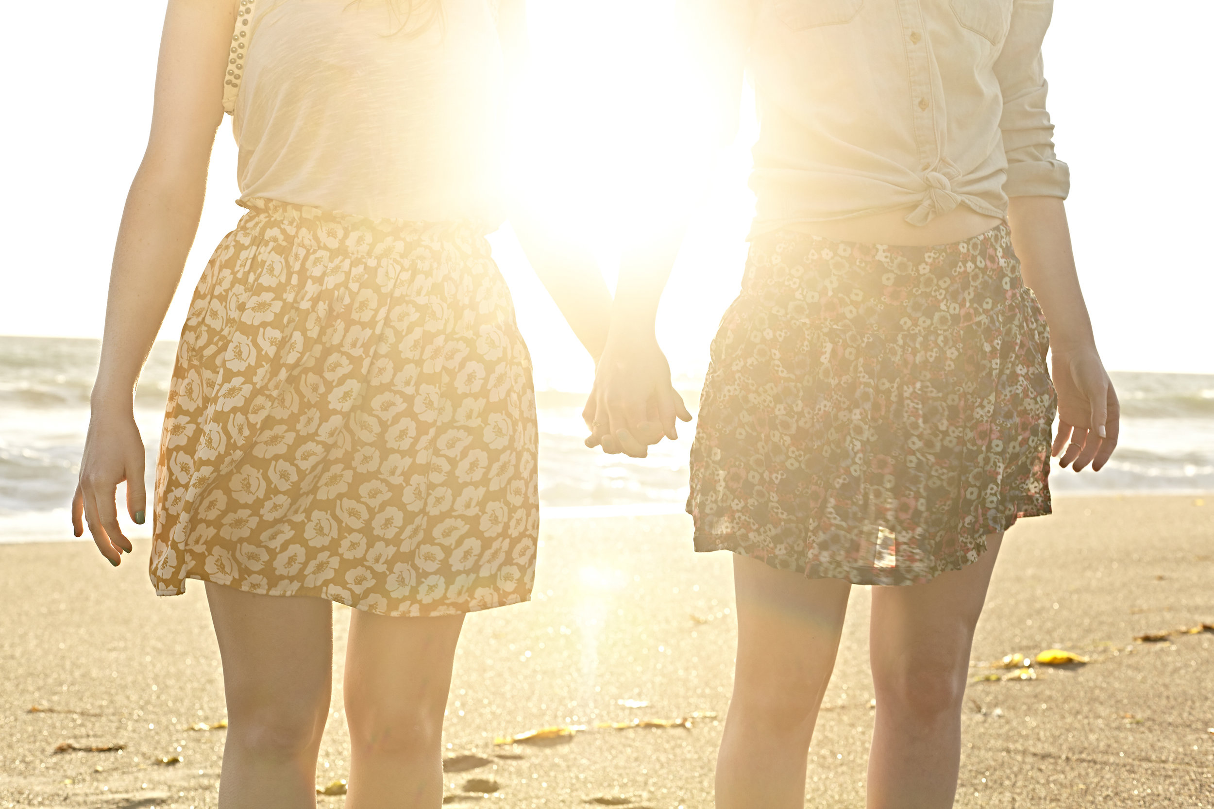 Two young women holding hands in the sunset at the beach