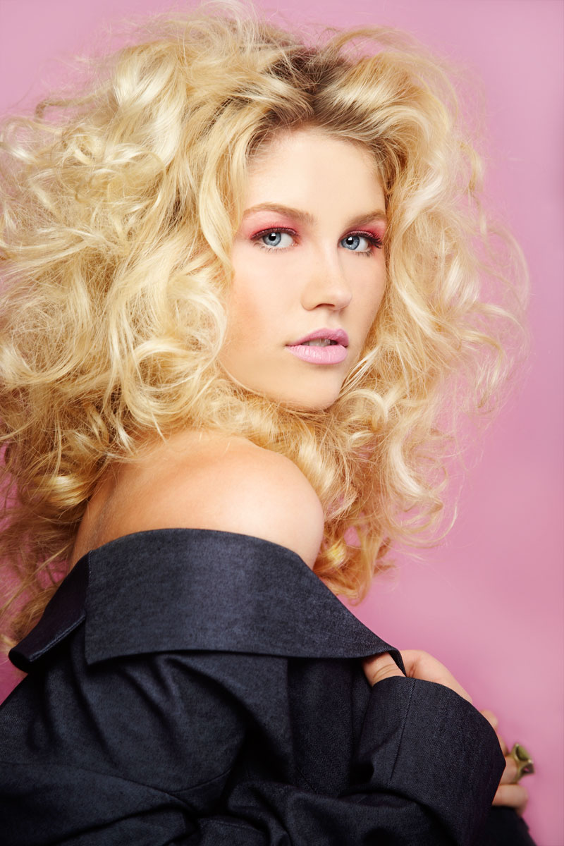 Fashion portrait of young woman with big curly blonde hair in blue jacket