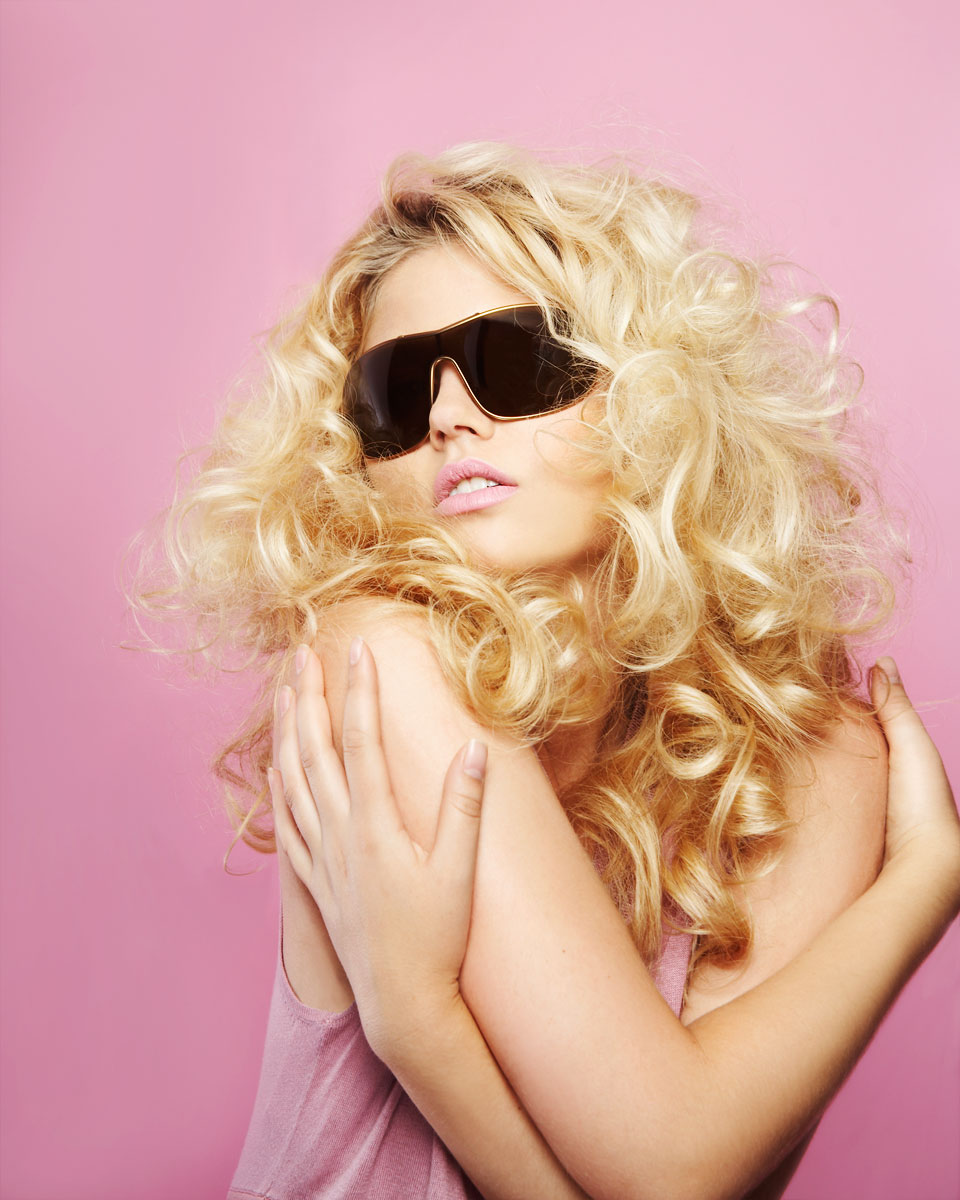 Fashion portrait of young woman with big curly blonde hair in sunglasses