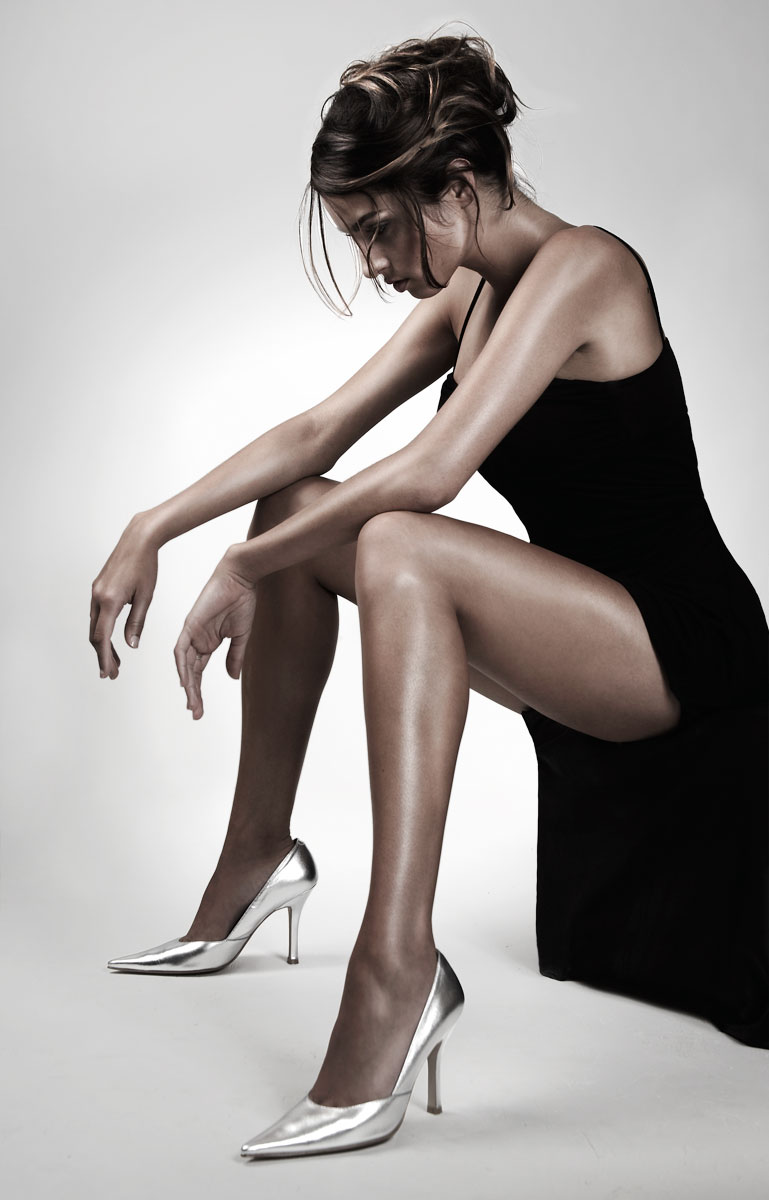 Young mixed race woman in little black dress and silver heels