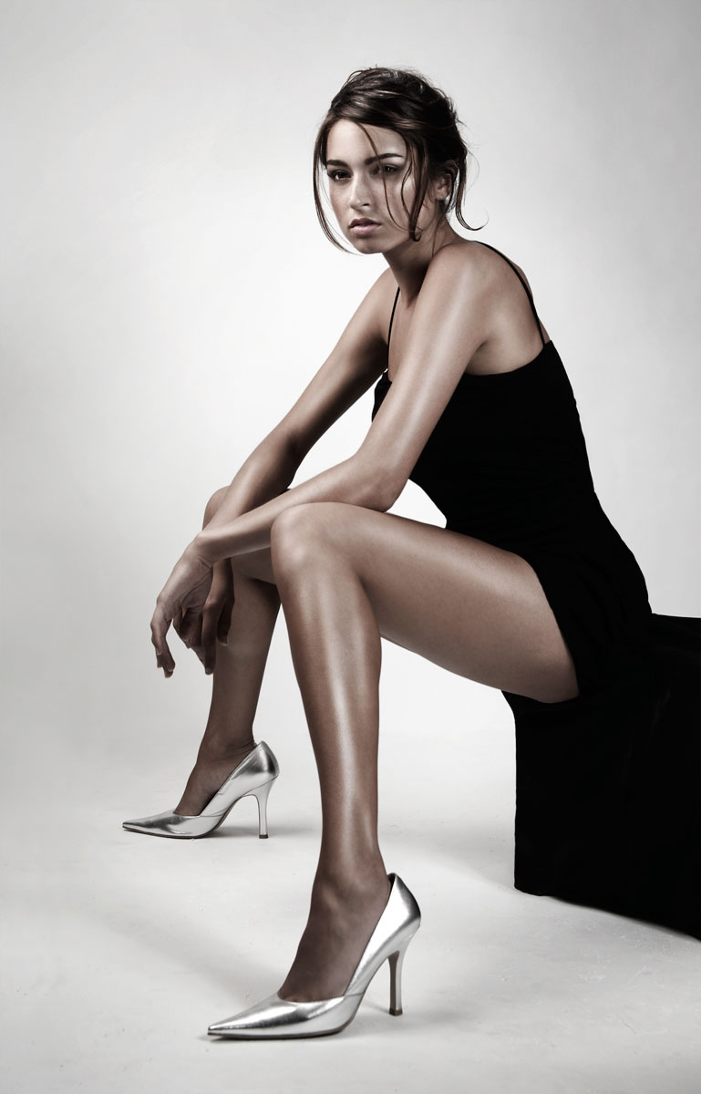 Young mixed race woman sitting in little black dress and silver heels