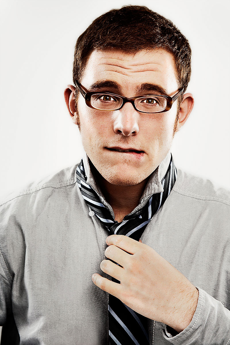 Young man in glasses tying his tie