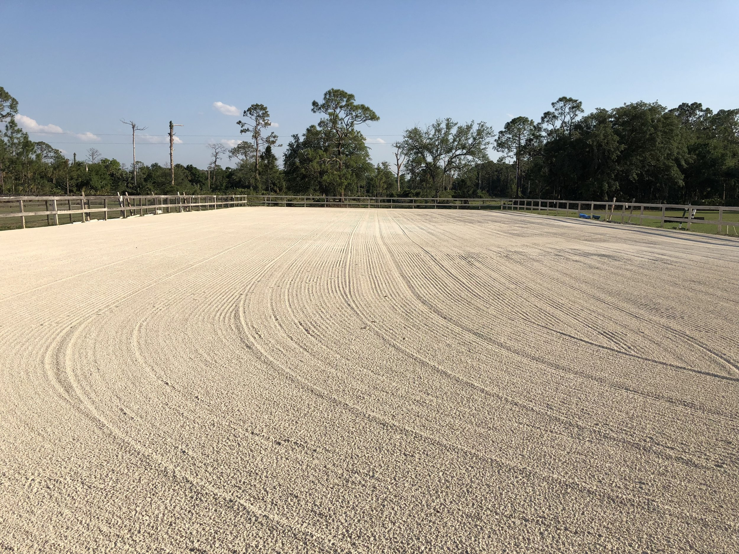 OPEN ARENA - The open arena near the farm entrance is also comprised of screenings, fenced and irrigated. It was renovated with new screenings in April 2018, and is typically used for both flatwork and jumping.