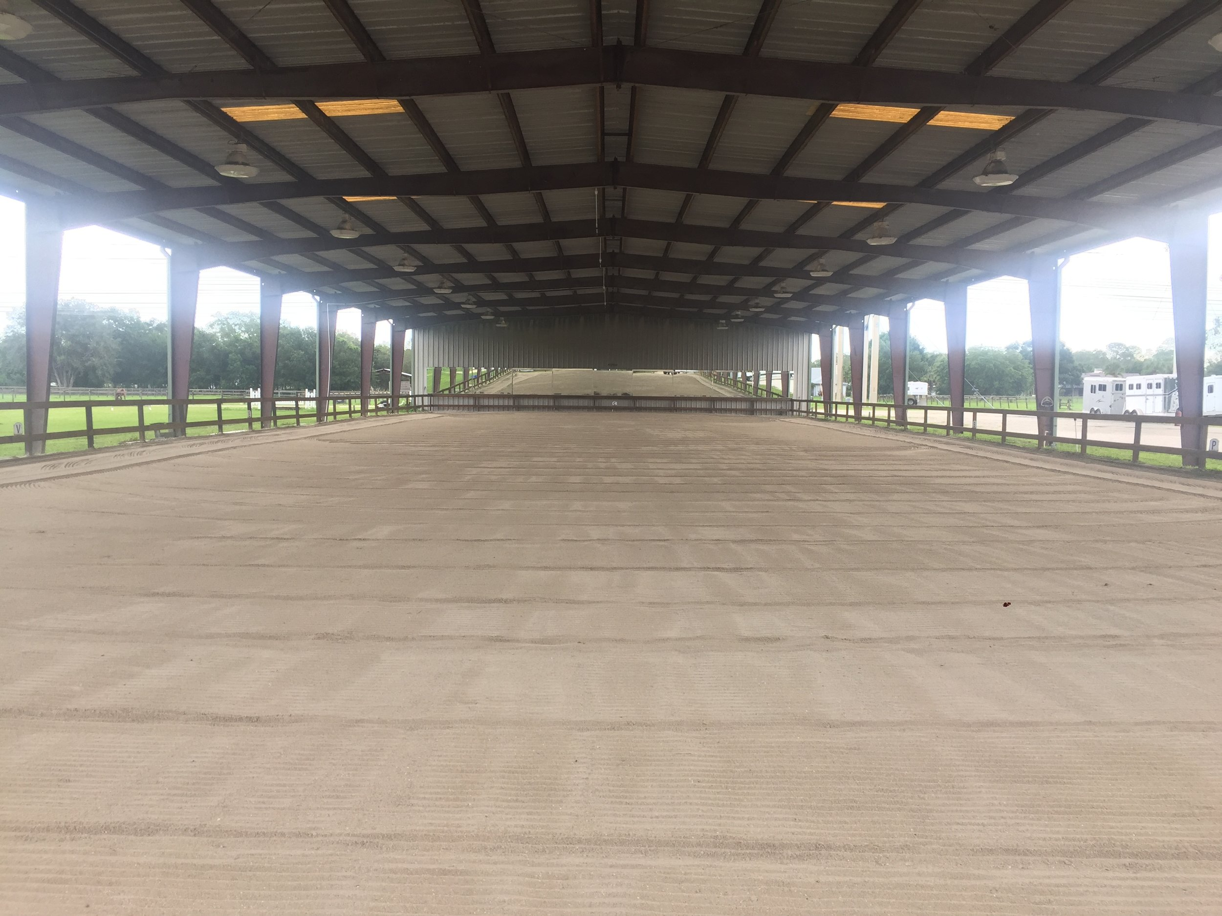 COVERED ARENA - The covered arena is fenced, lighted, irrigated, and has mirrors. The footing is screenings that are groomed thoroughly each day with our tractor and TR3 E-Series Rake. This arena is normally used for flatwork only.