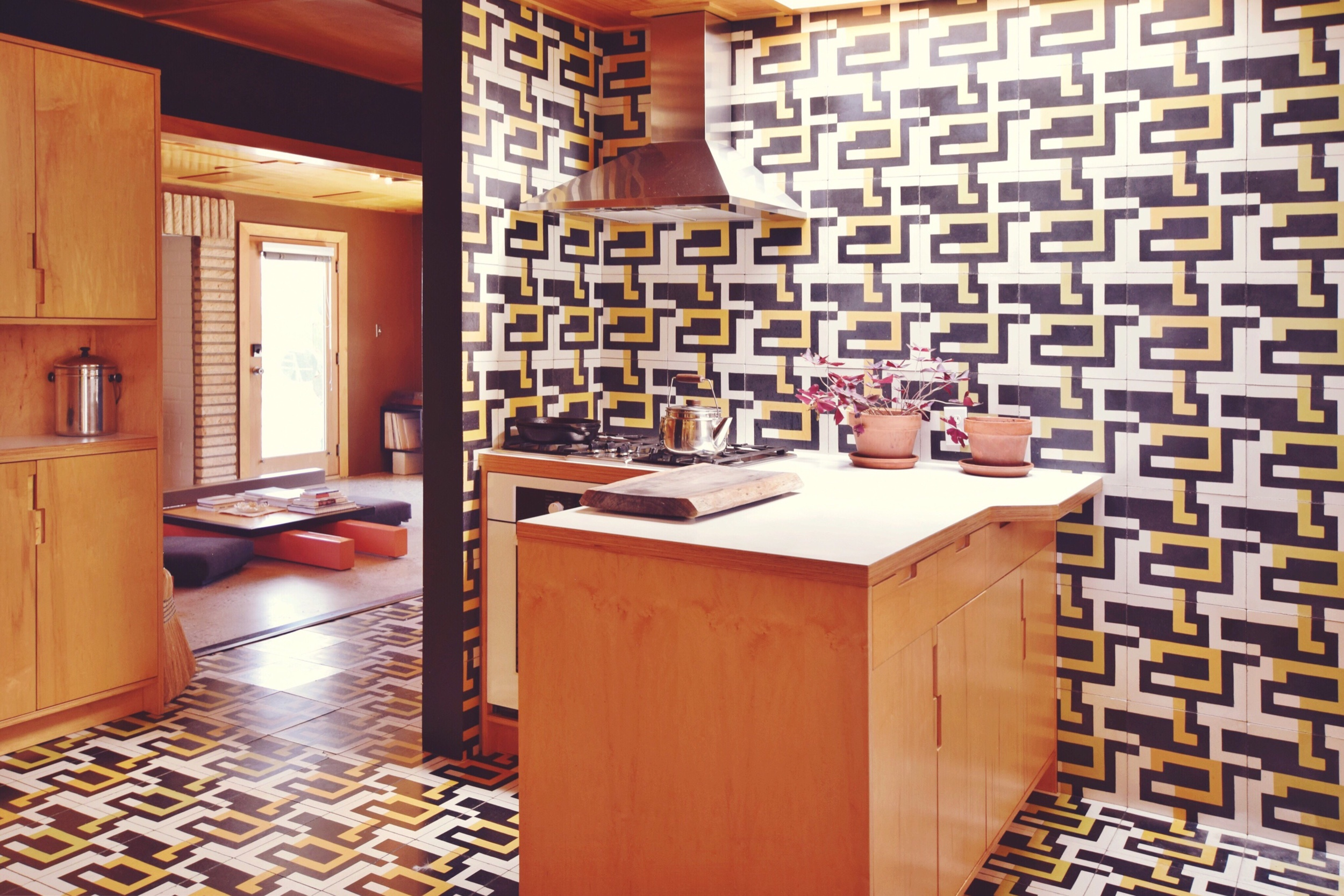 The kaleidoscopic kitchen featuring Andrea's custom tiles and work benches. A reluctant diner, Andrea lived without a stove for many years, cooking instead together with her guests on a communal hot plate similar to a Korean BBQ.