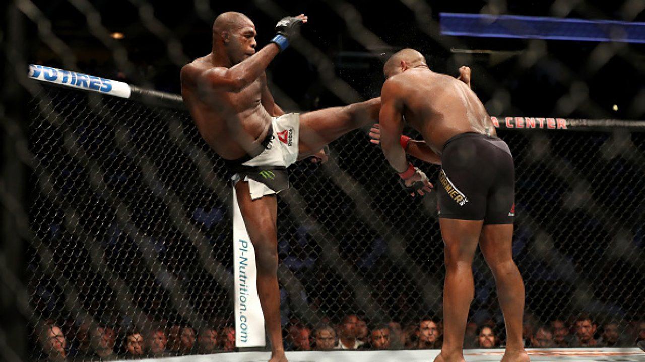 Jon Jones (white shorts) head kicks Daniel Cormier (black shorts) at UFC 214. [Credit: Pundit Arena]