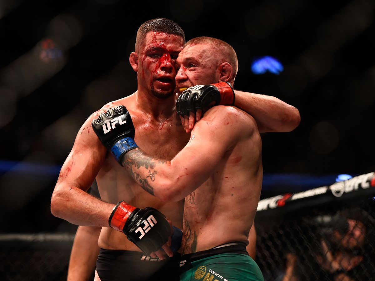 Nate Diaz (black shorts) and Conor McGregor (green shorts) embracing after fight at UFC 202. [Credit:Getty Images]