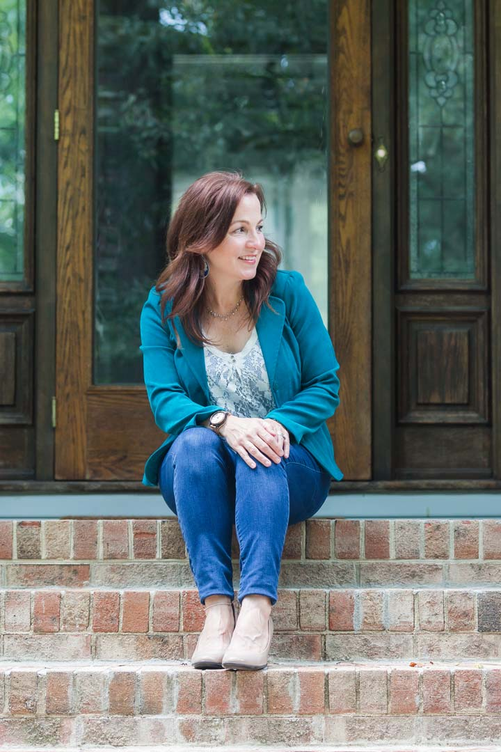 Melissa Bell, a Christian Women's speaker, sitting at the front steps of her home