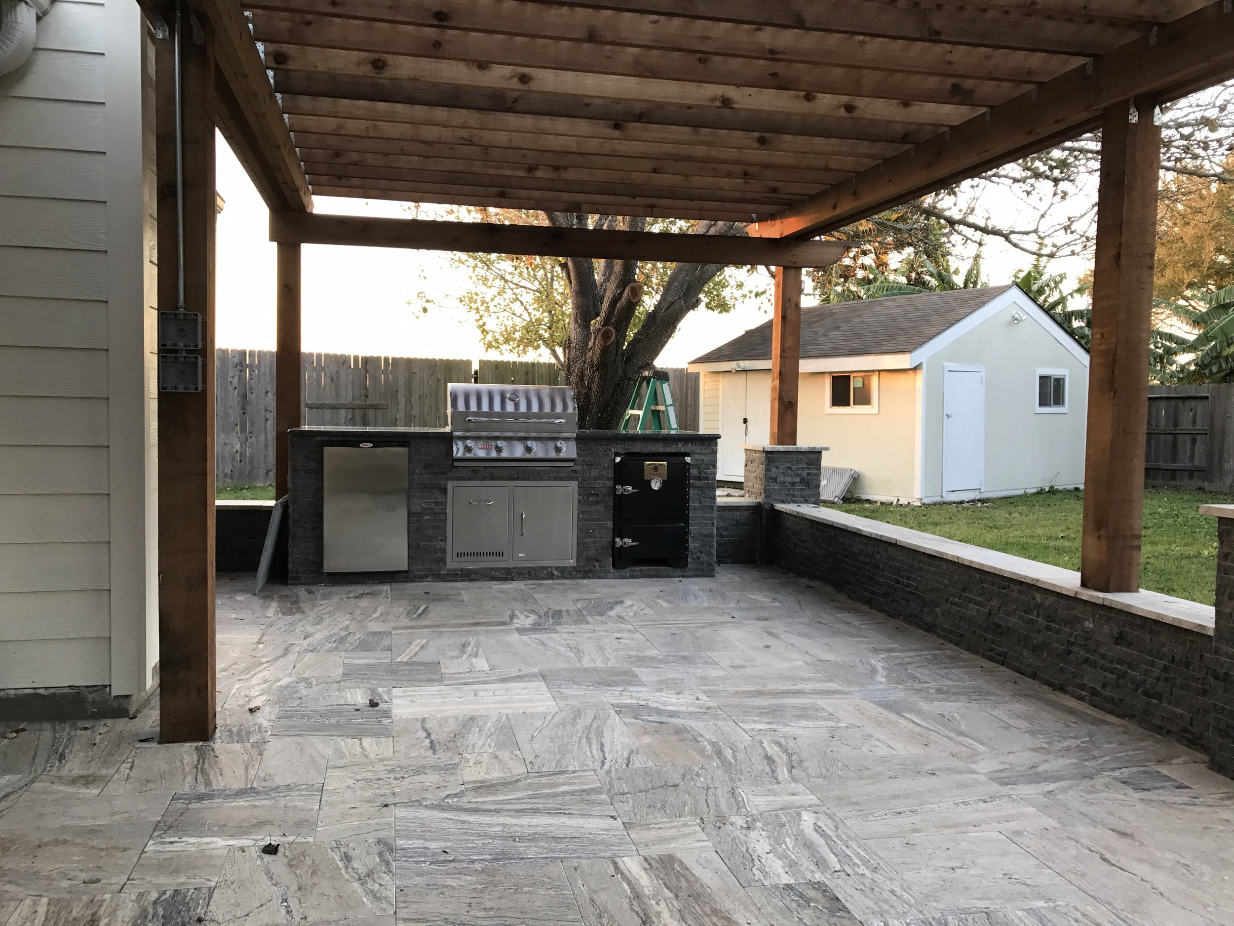 outdoor kitchen with travertine paver deck and pergola