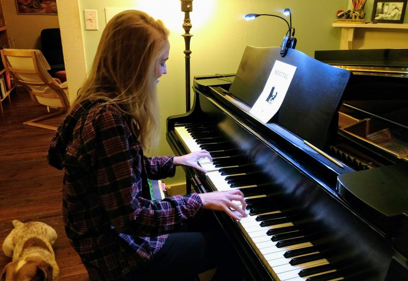 A student enjoying the piano with Bentley, my mascot, beside her.