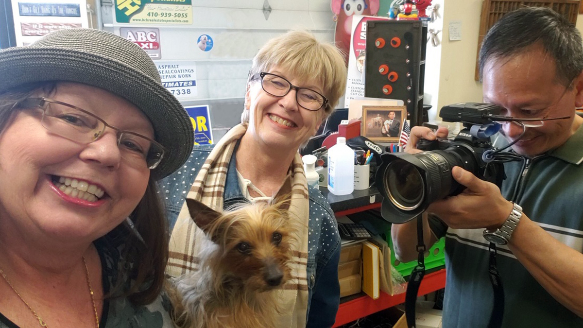 """Kathi Santora (c) on assignment for Harford Magazine and the feature story   Loosening their collars: Schools and businesses that have pets who """"work"""" in the office   .  (L) Paula Cassagrande, owner of Big House Signs in Havre de Grace (with Shorty) and Ken Lam, Baltimore Sun photographer."""