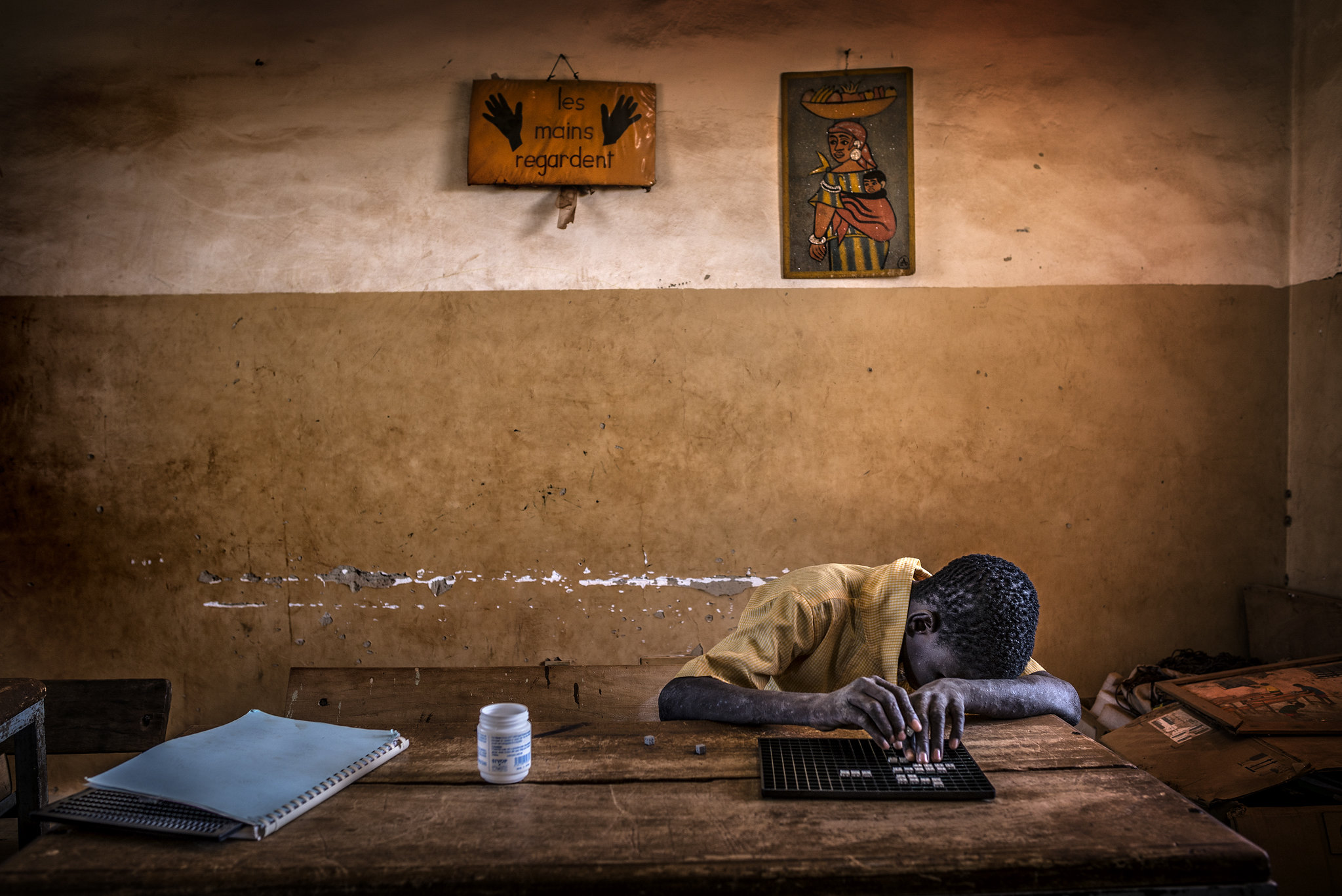 A blind boy does his homework at a very humble school for blind children outside Ouagadougou, Burkina Faso (West Africa). The Hands Look (Les Mains Regardent) for those who want to see and learn. The craving for knowledge knows no bounds. The passion for  Submitted by: Antonio Aragon Renuncio
