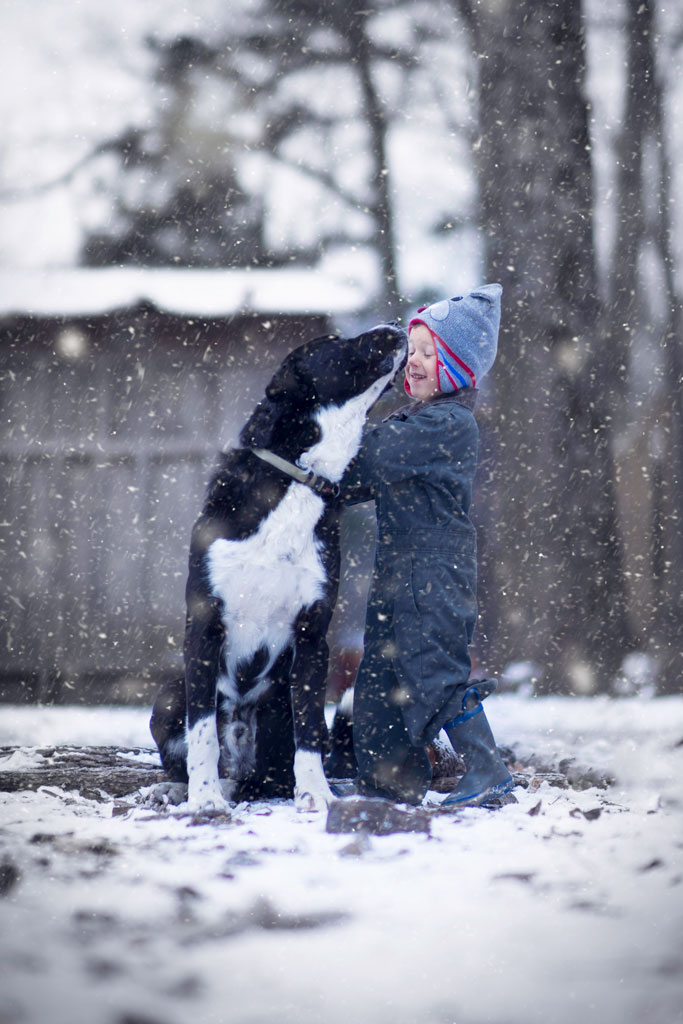 little-boy-playing-with-dog-in-the-snow.jpg