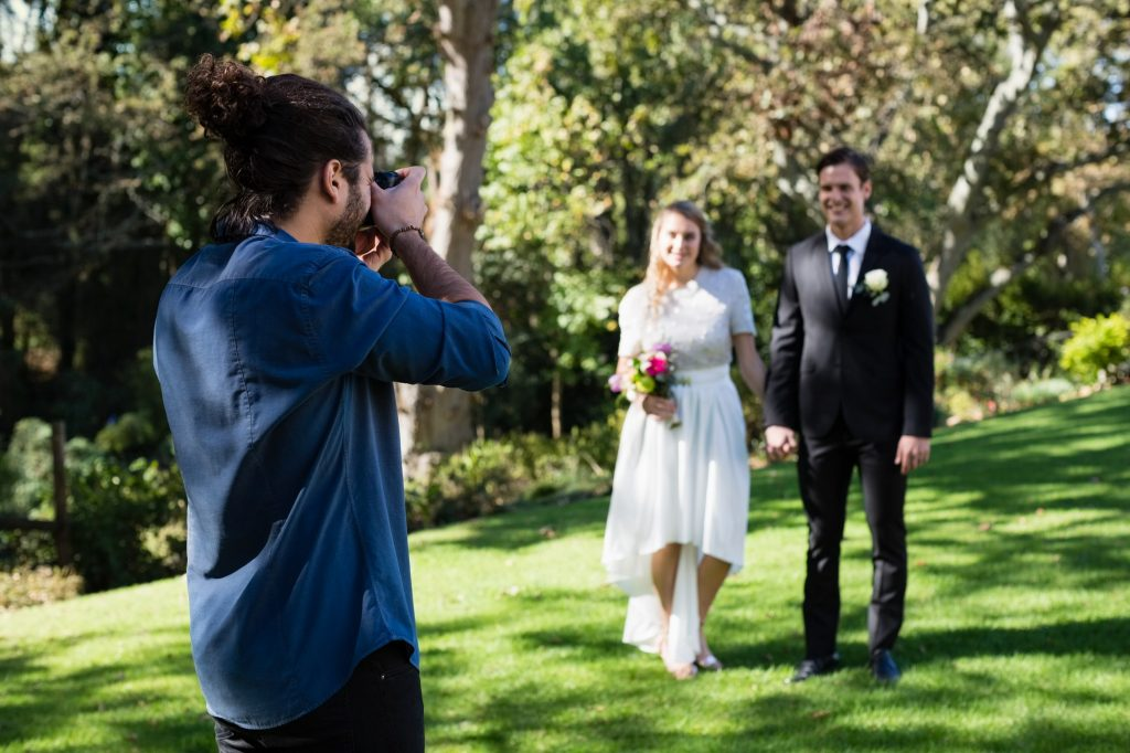 Photographer taking photo of newly married couple